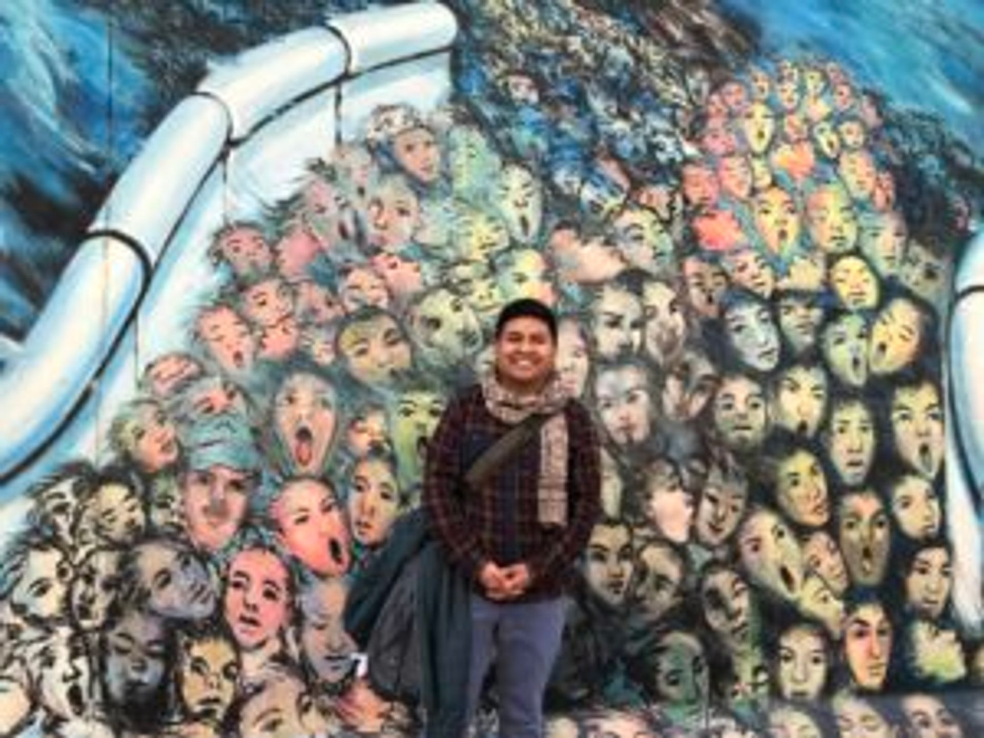Camilo stands in front of a Berlin wall mural.