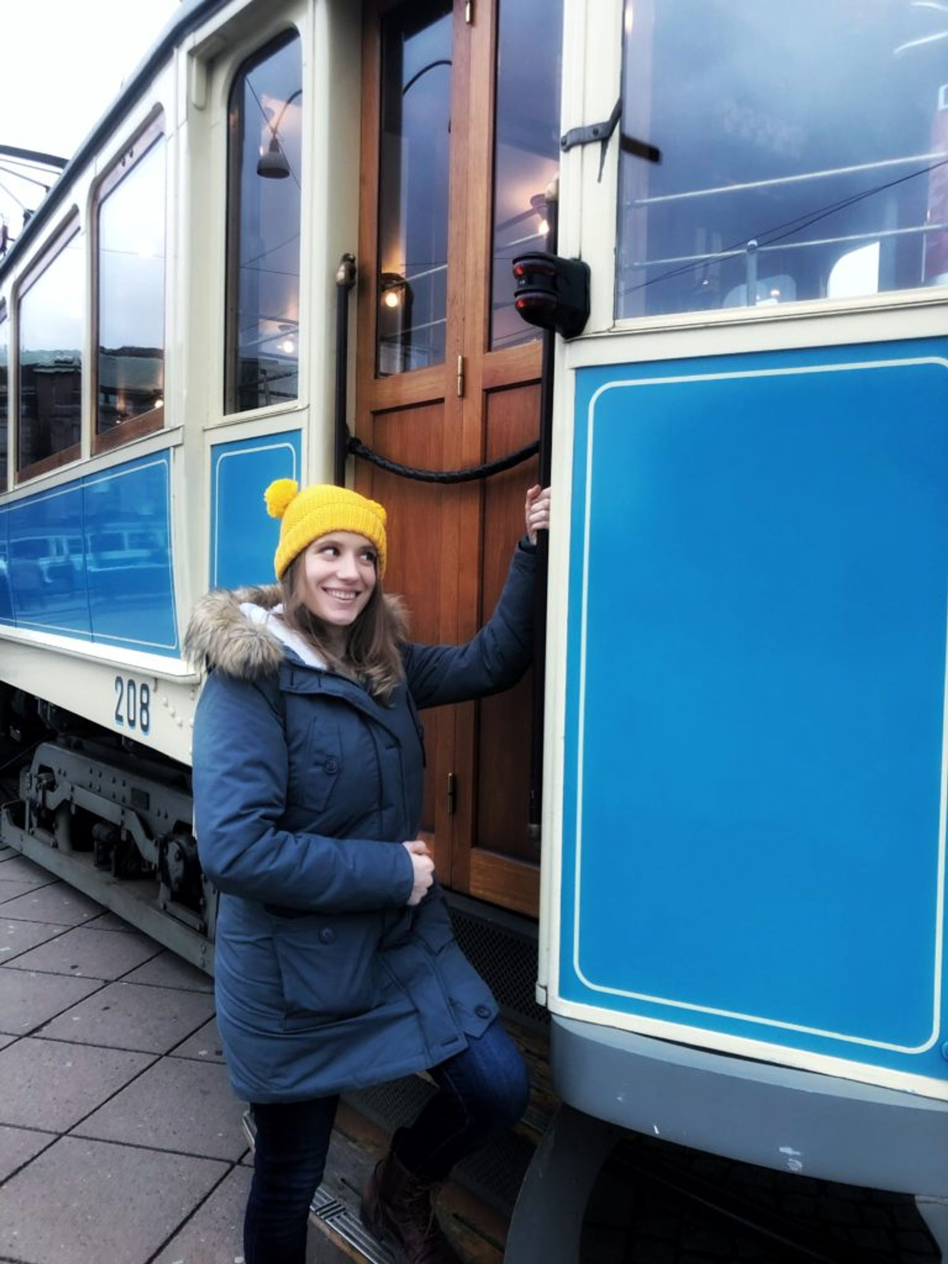 A person standing beside a blue tram.