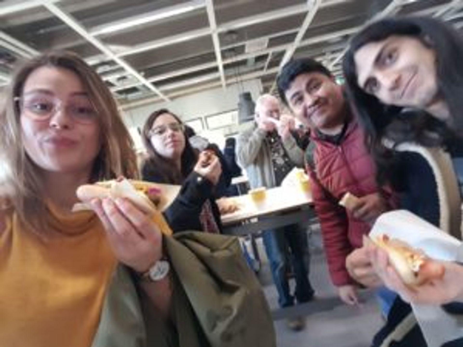 Camilo and several friends eat hotdogs in IKEA.