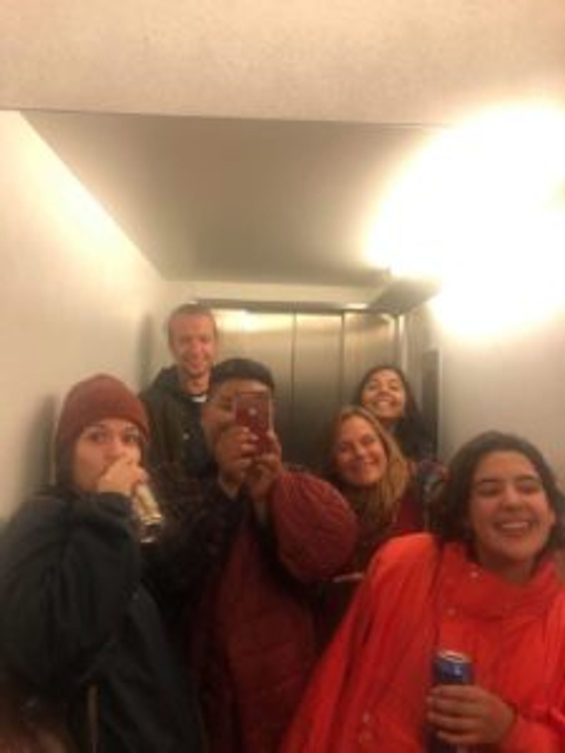 A group of people standing in a lift.