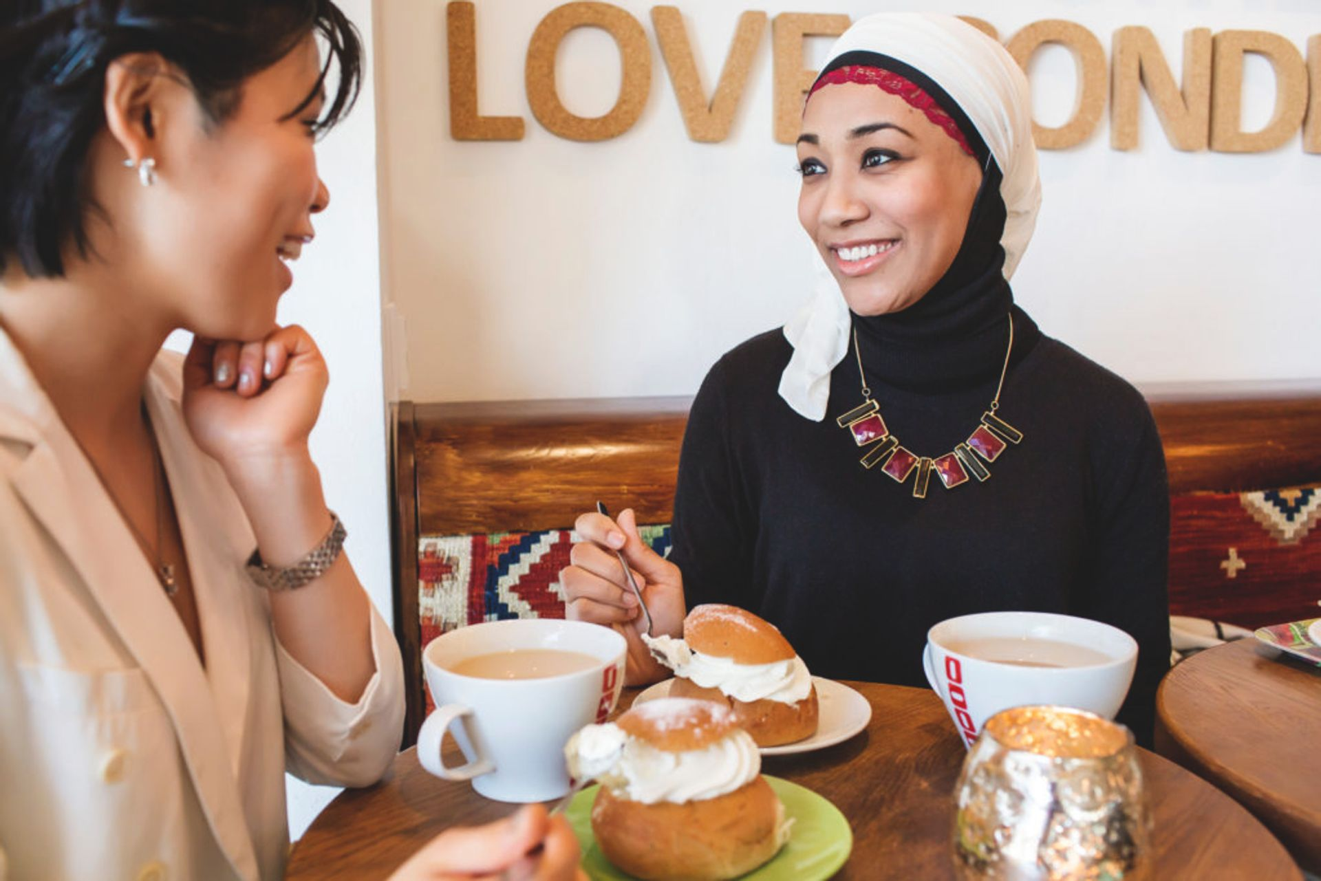 Two women sitting in a cafe drinking coffee and eating semlor - traditional Swedish pastries eaten on Shrove Tuesday.