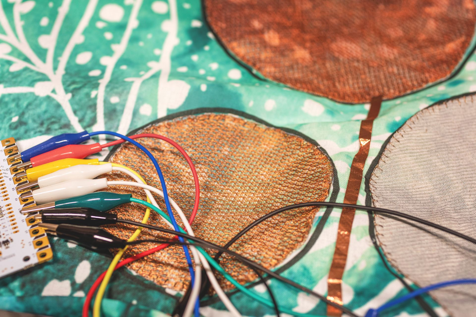 Copper wires weaved into blue textiles.