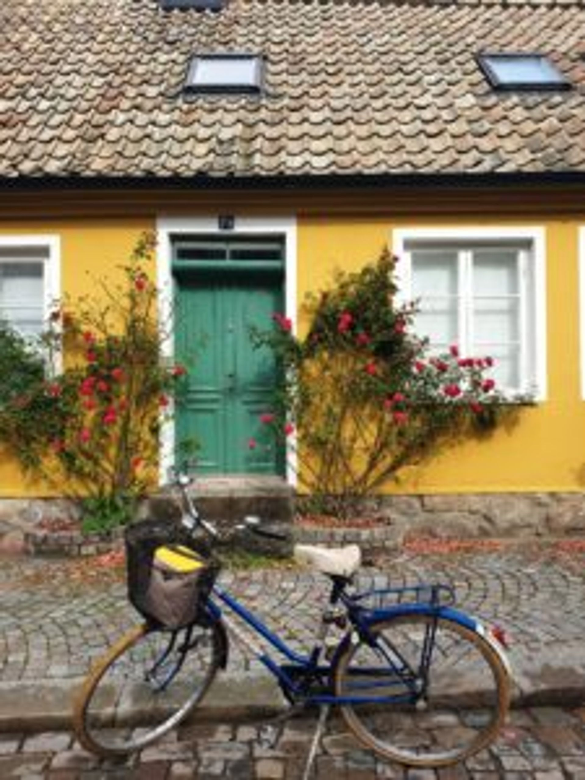 A blue bicycle is parked on a cobbled steet outside a small, yellow house.
