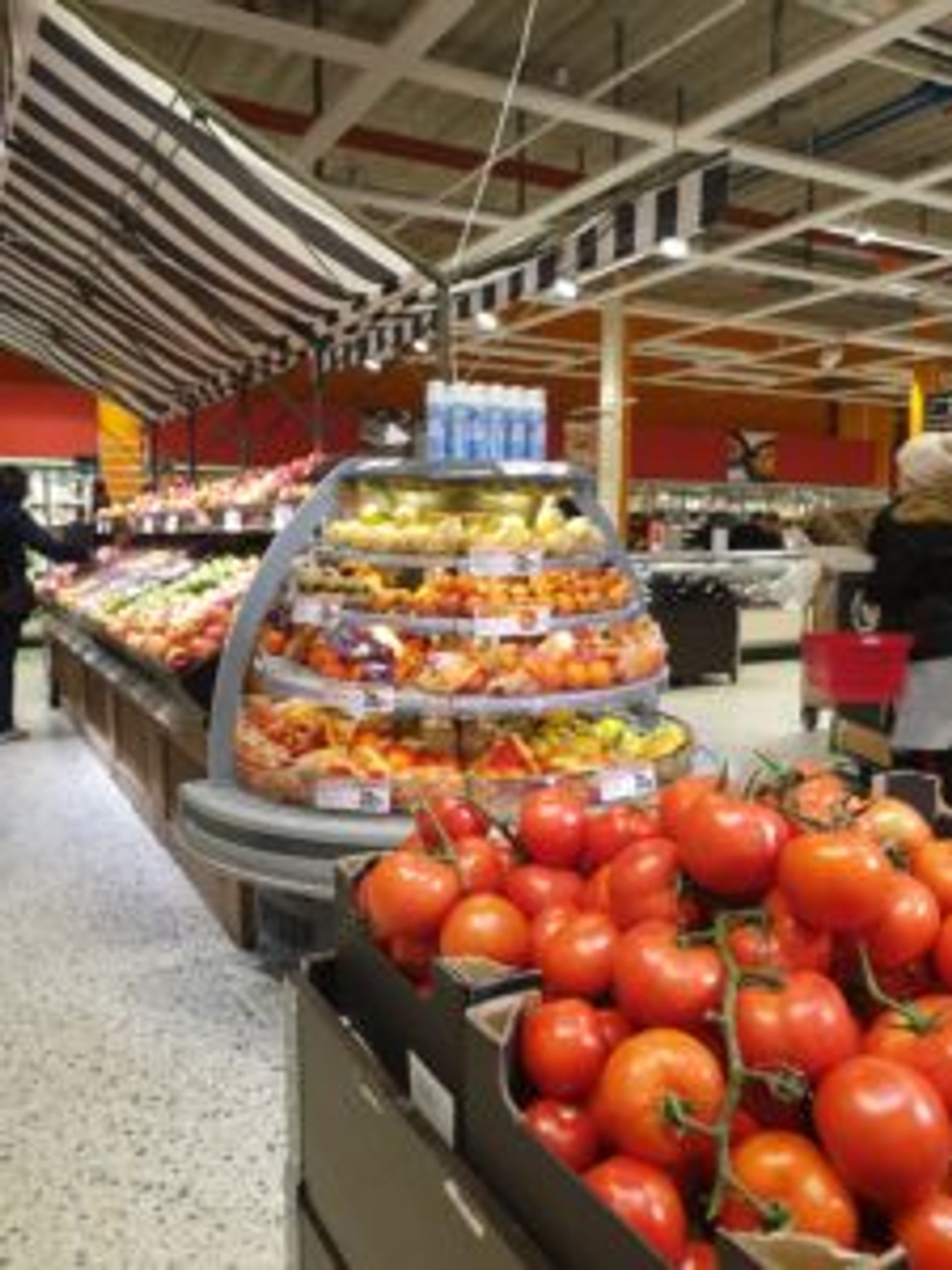 Aisles of fresh fruit and vegetables in a supermarket.