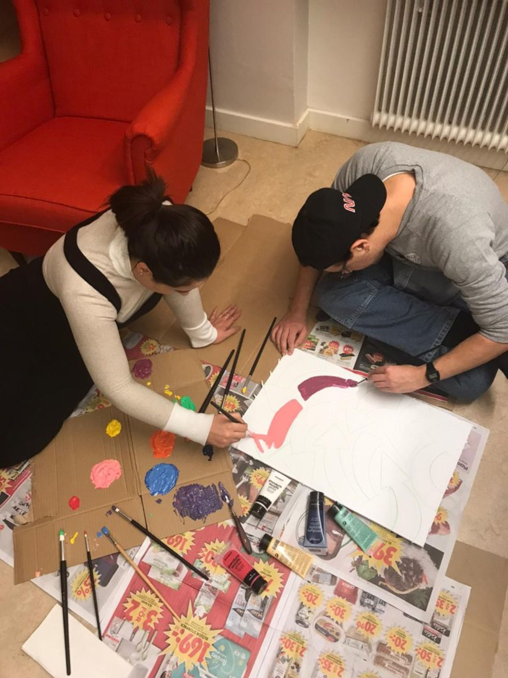 Two students sitting on the floor painting on a white piece of paper.