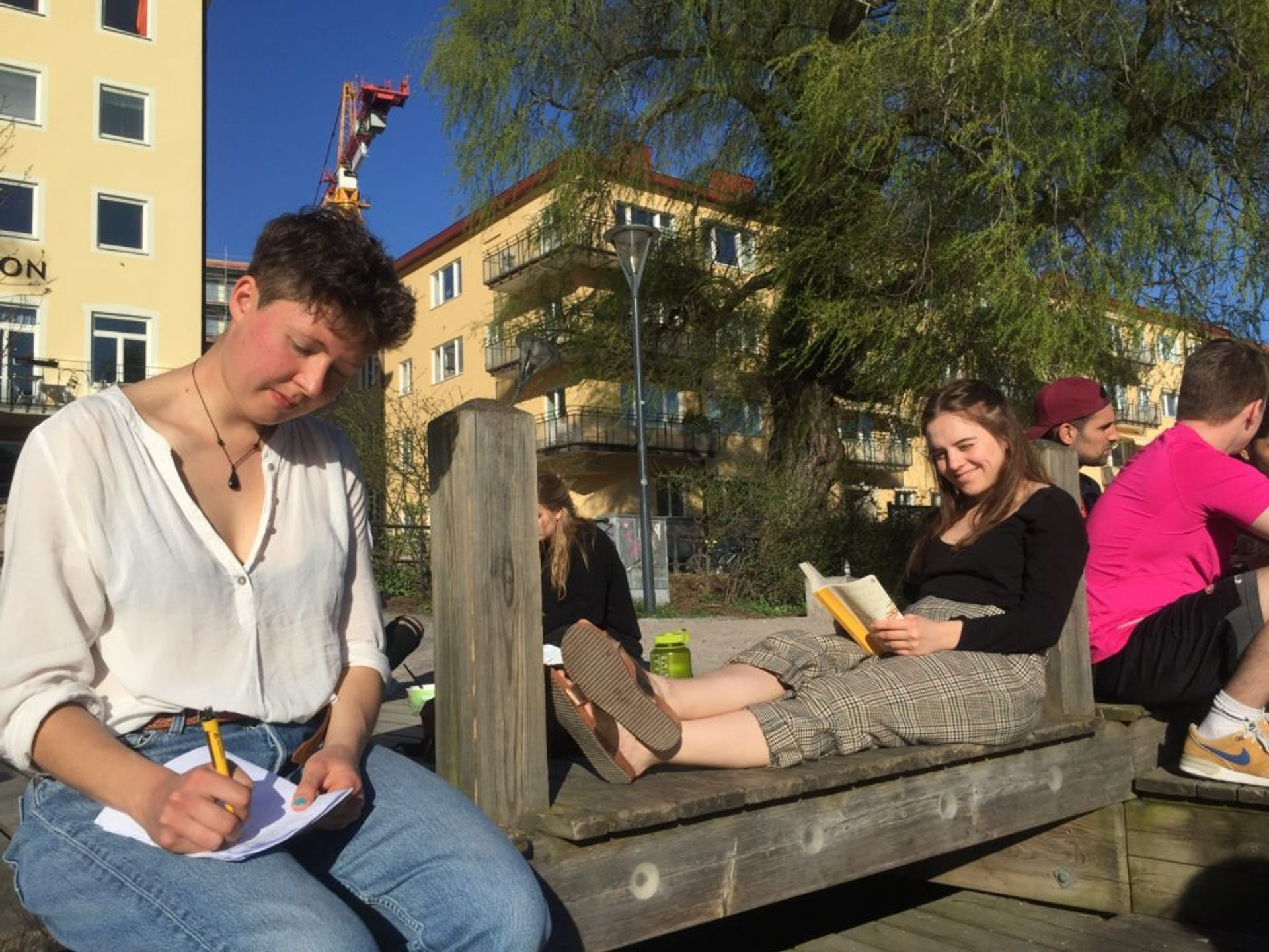 Two students sitting on wooden steps by the river reading and taking notes.
