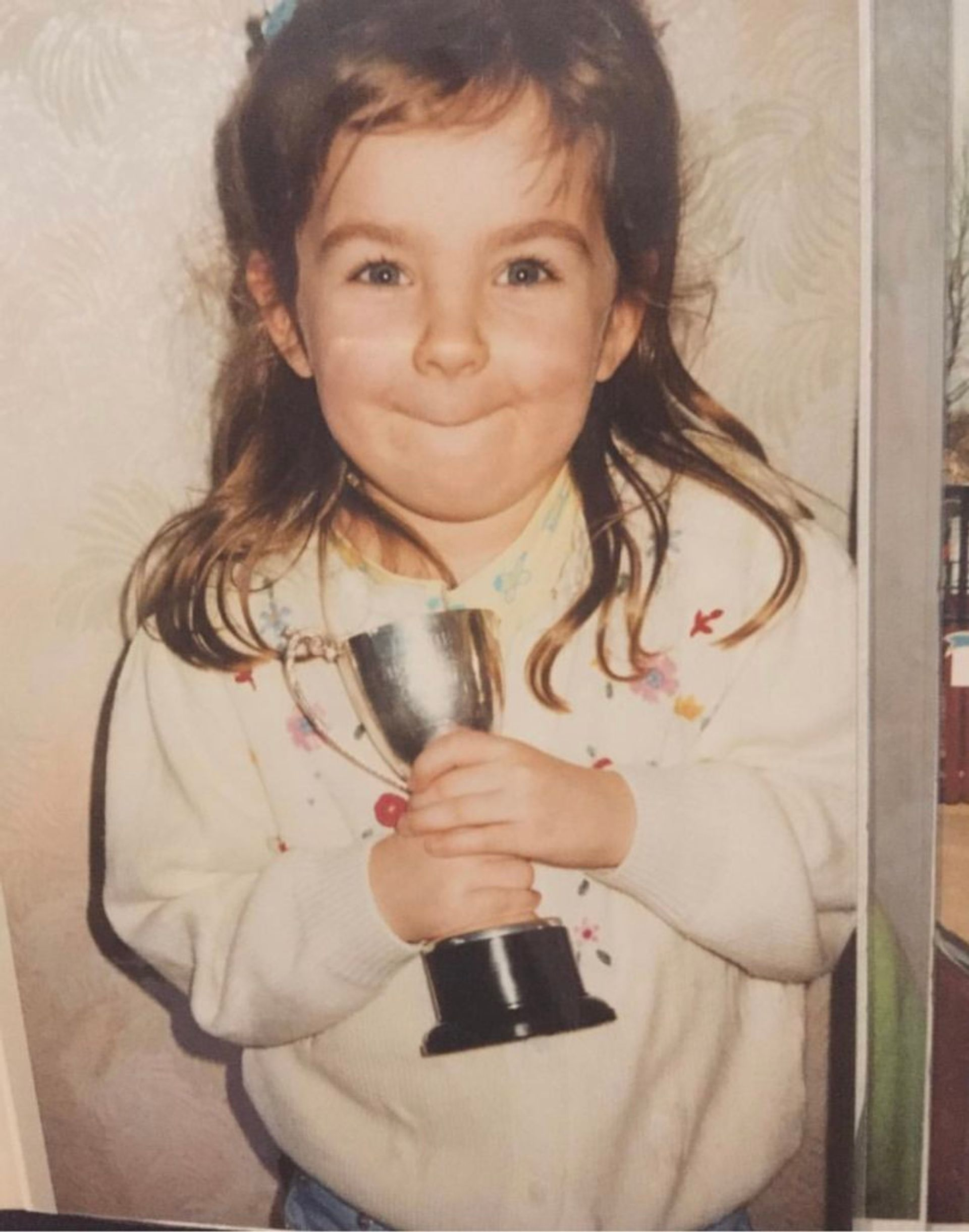Emma as a child. She is wearing a white sweater and holding a little trophy.