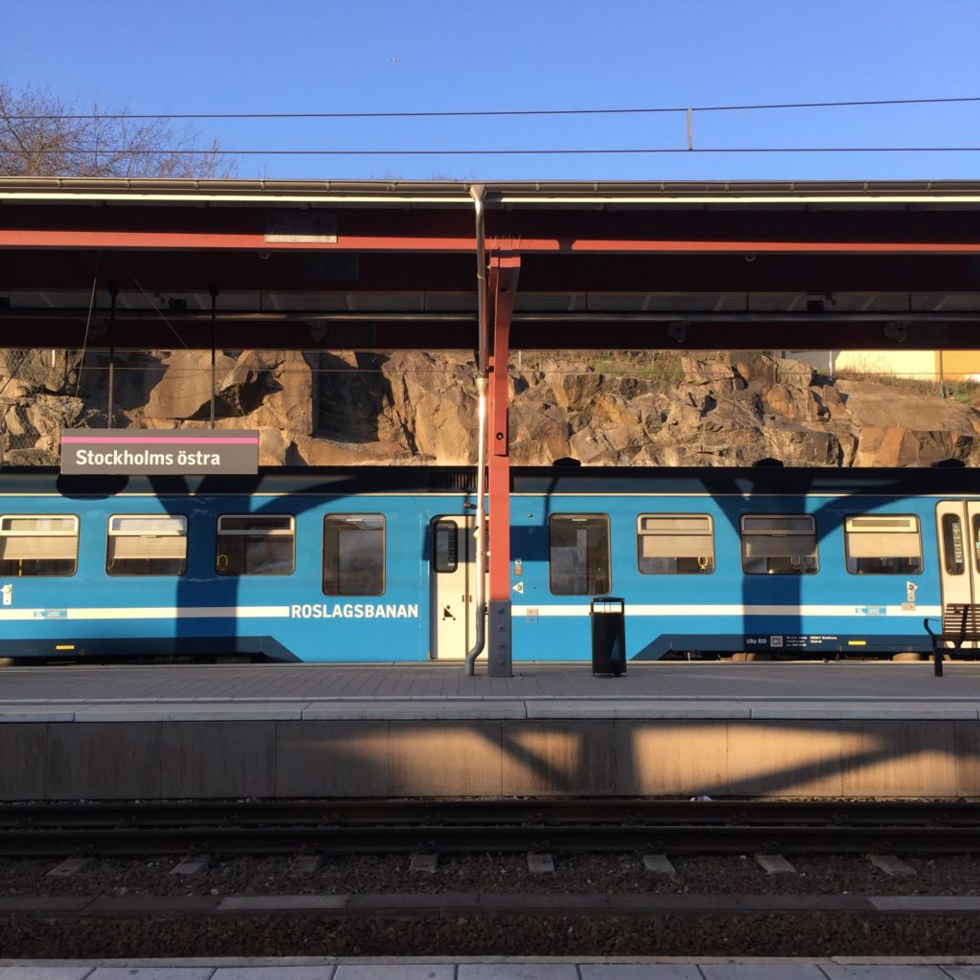 A blue commuter train standing still at a train station in Stockholm.