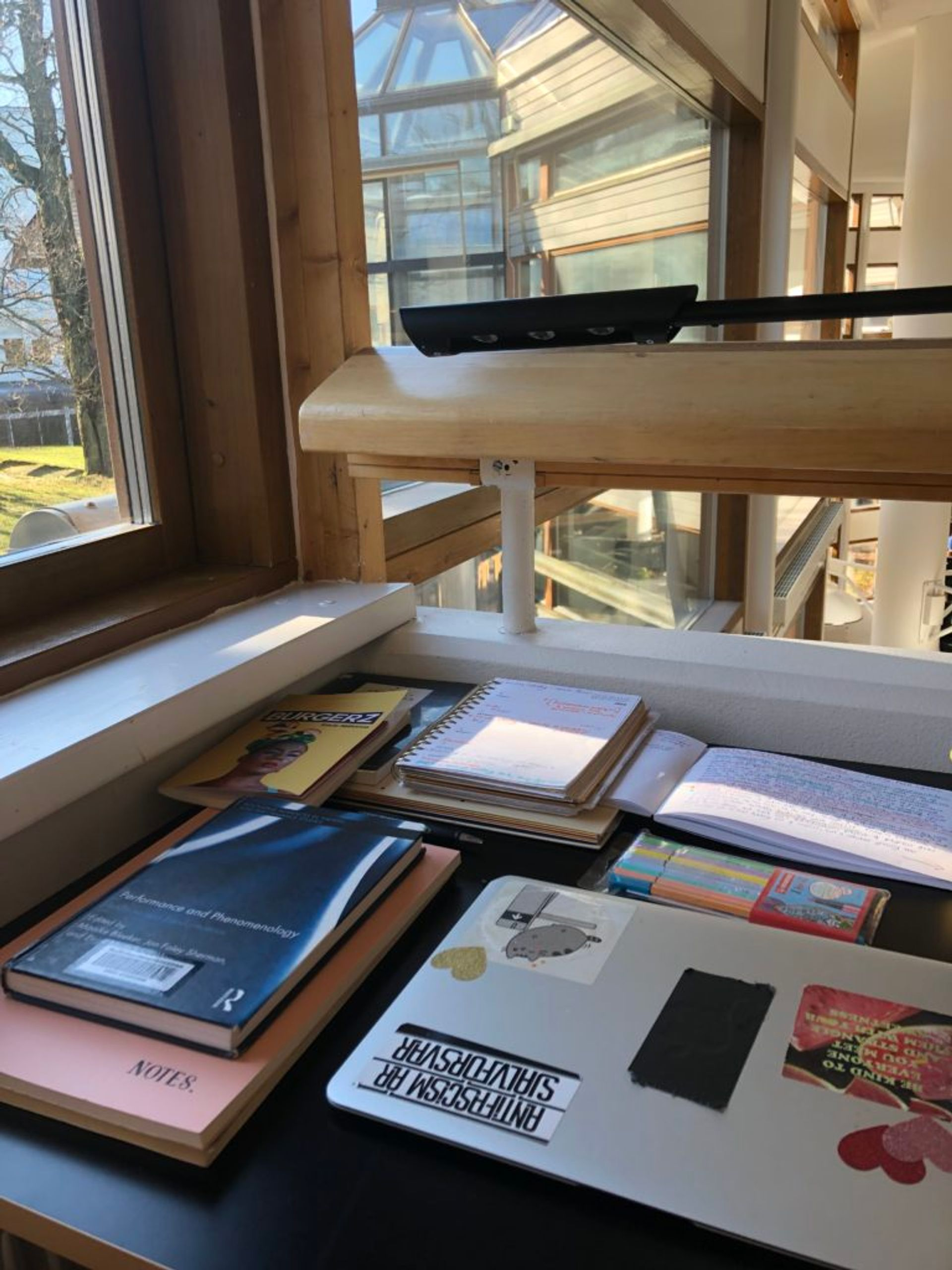 Several library books, notebooks and a laptop on a desk in the Stockholm University library.