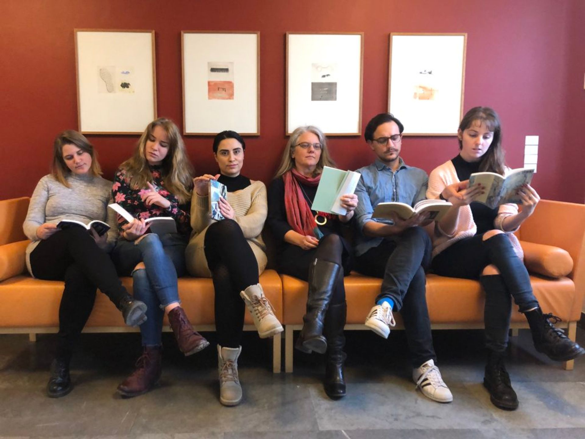 Emma sits with her teacher and coursemates on a sofa, reading books, clearly posing for the photo.