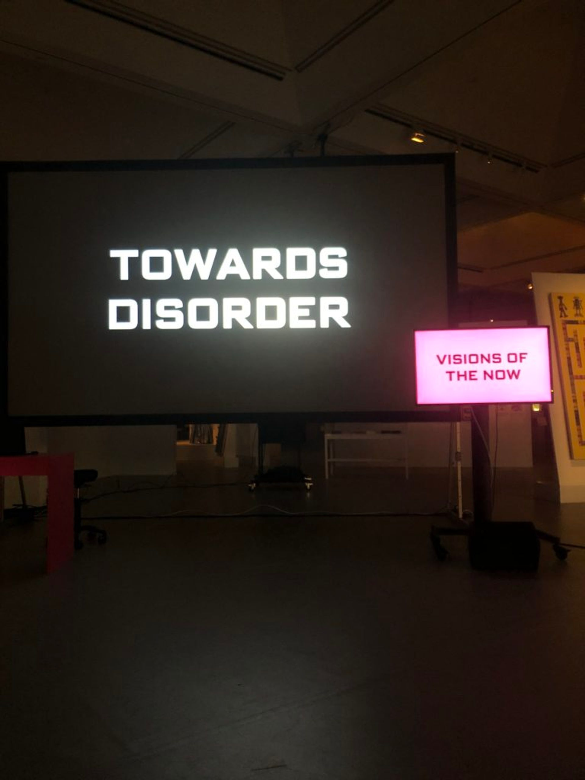 A performance art lecture. There are two screens, captions read 'Towards disorder' and 'Visions of the now'.