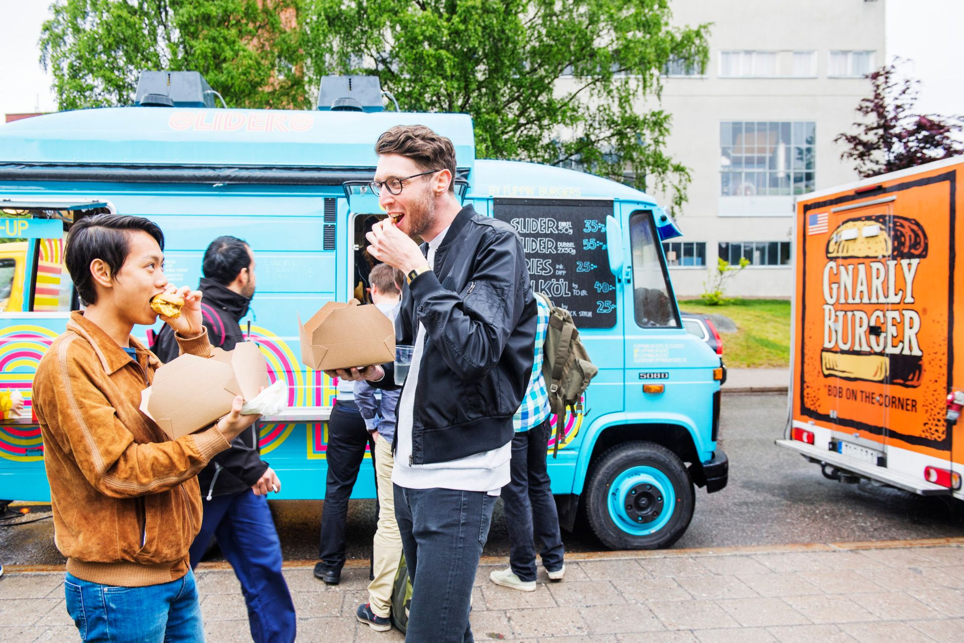 Students standing outside eating food from a light blue food truck.