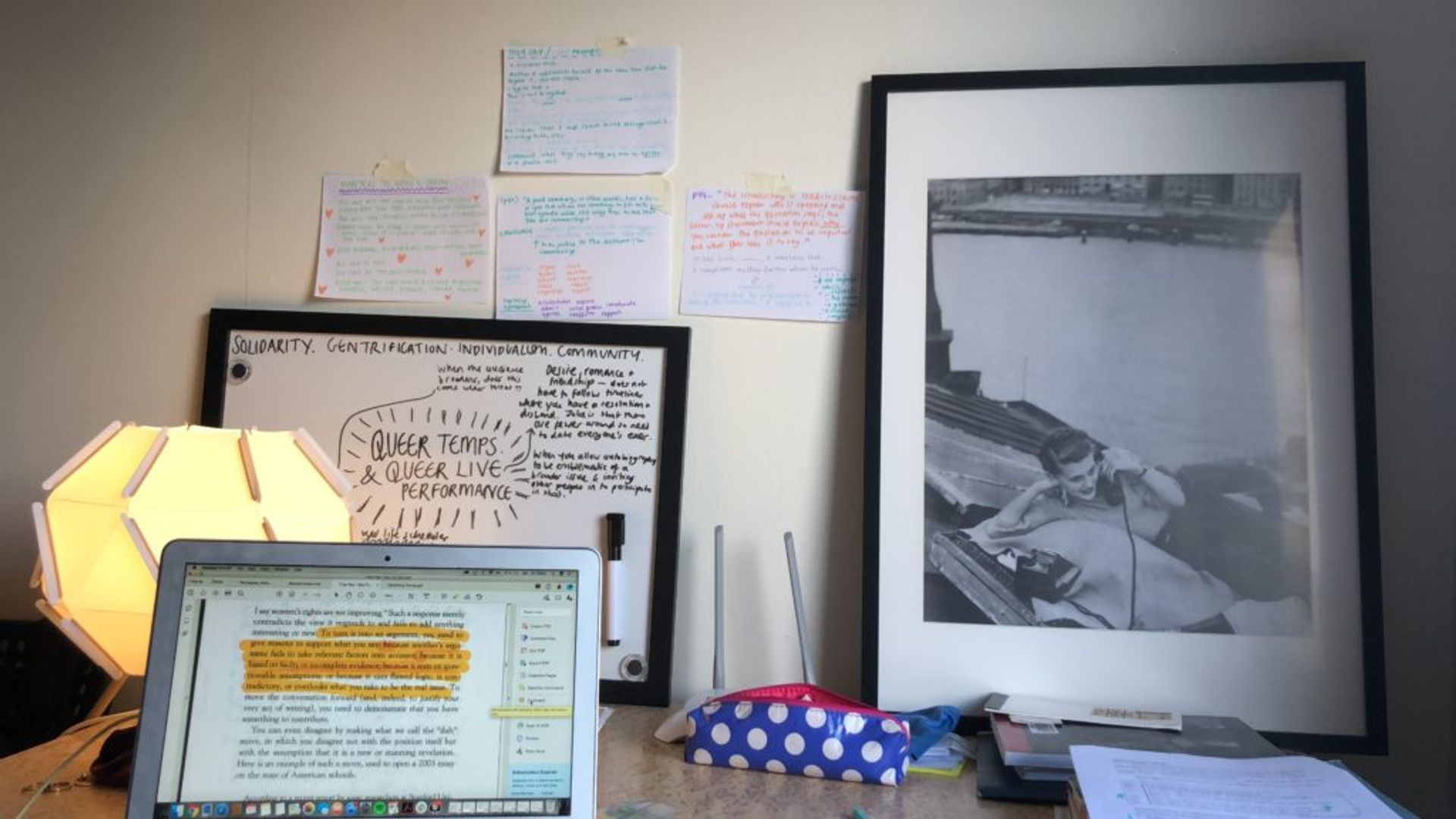Emma's study station, featuring a laptop, notes, books and a lamp.
