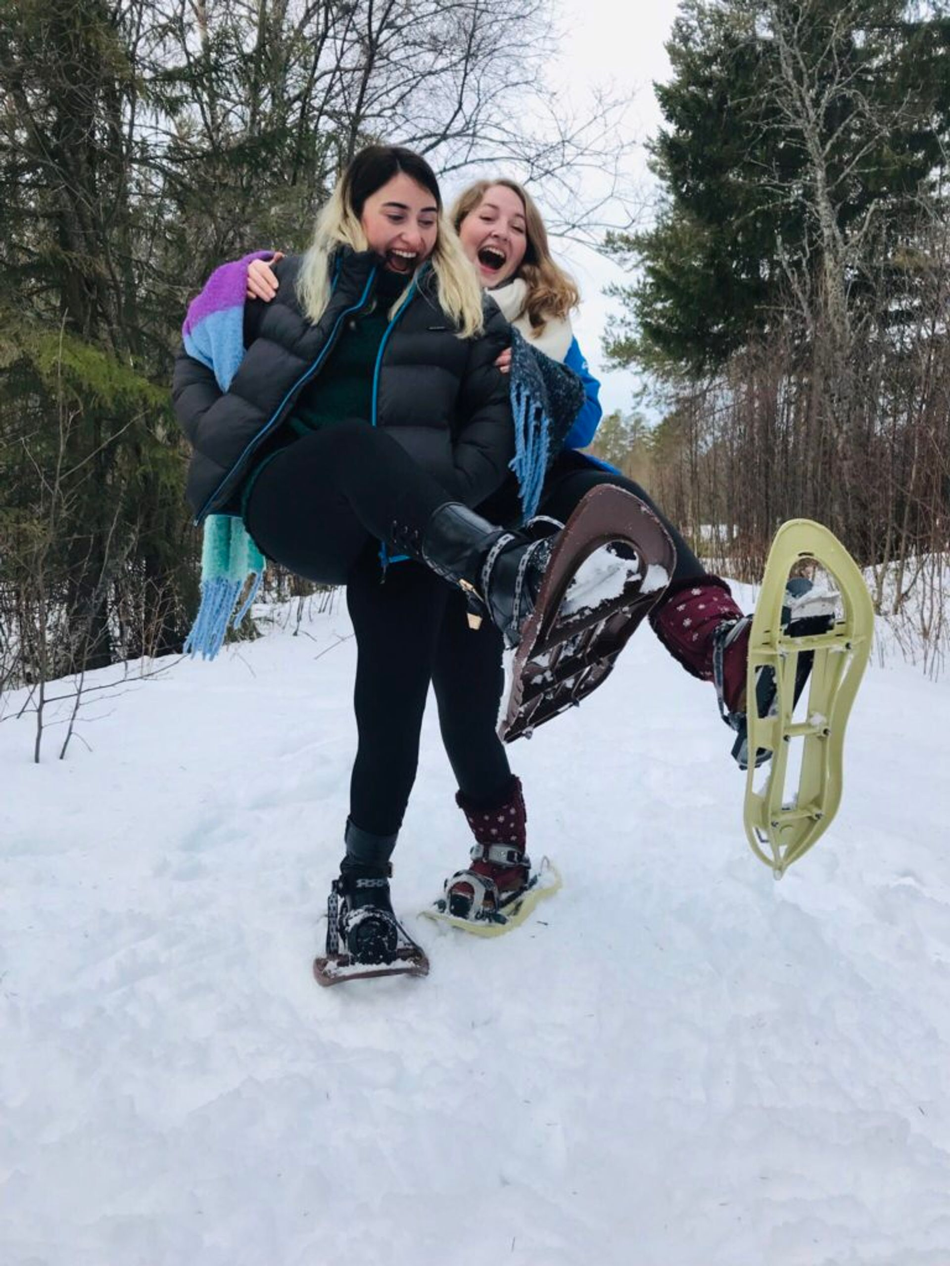 Hazal and Katharina standing in the snow wearing snowshoes.