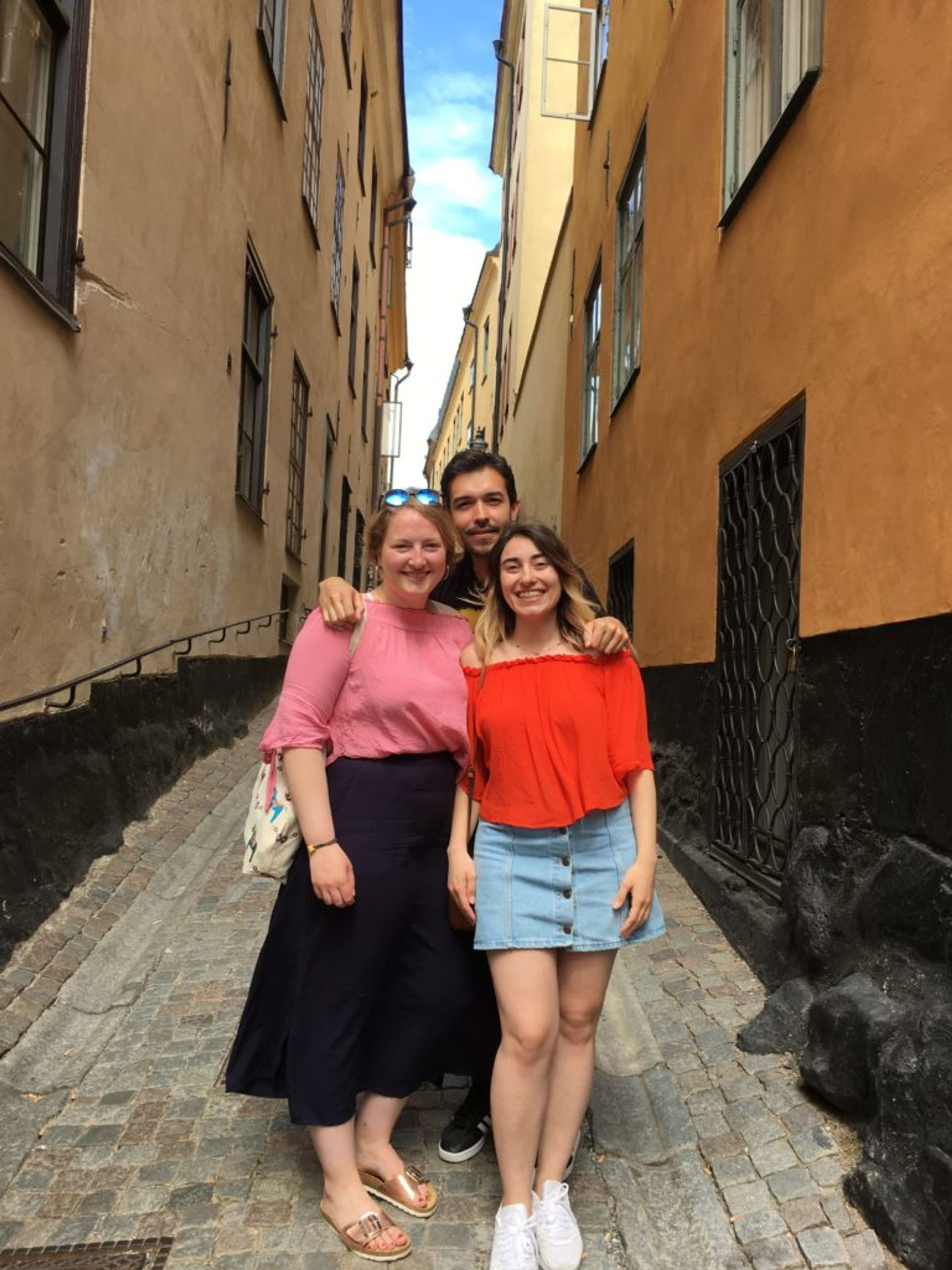 Hazal and two friends, Katharina and Daniel, standing close together on a cobbled street in Stockholm's Old Town.