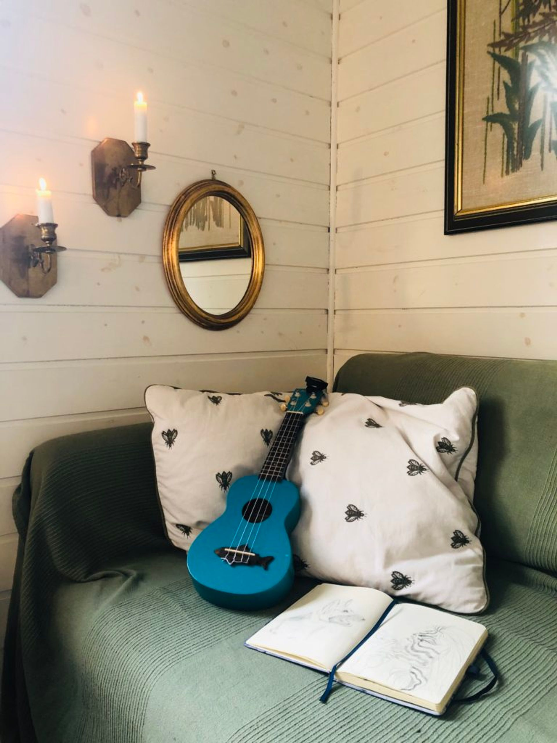 A sofa, covered in a green blanket. On the sofa are two cushions, a blue ukelele and a notebook.
