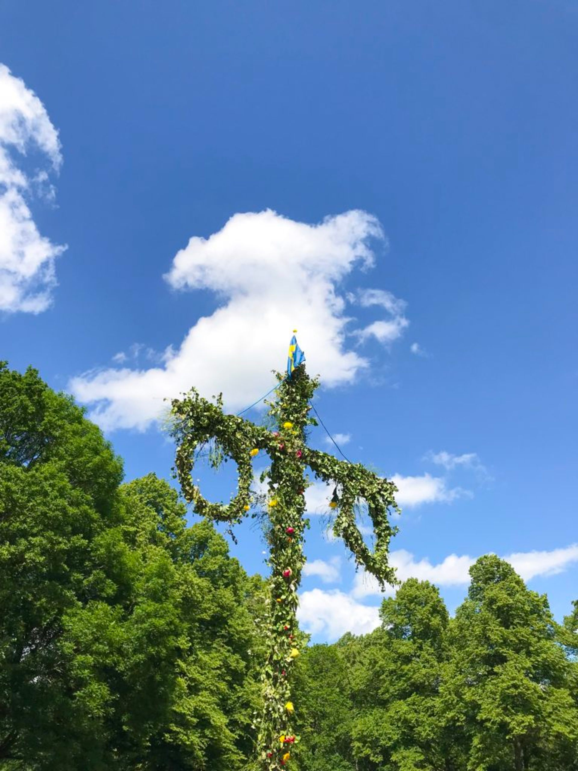A traditional Midsummer maypole covered in leaves and flowers.