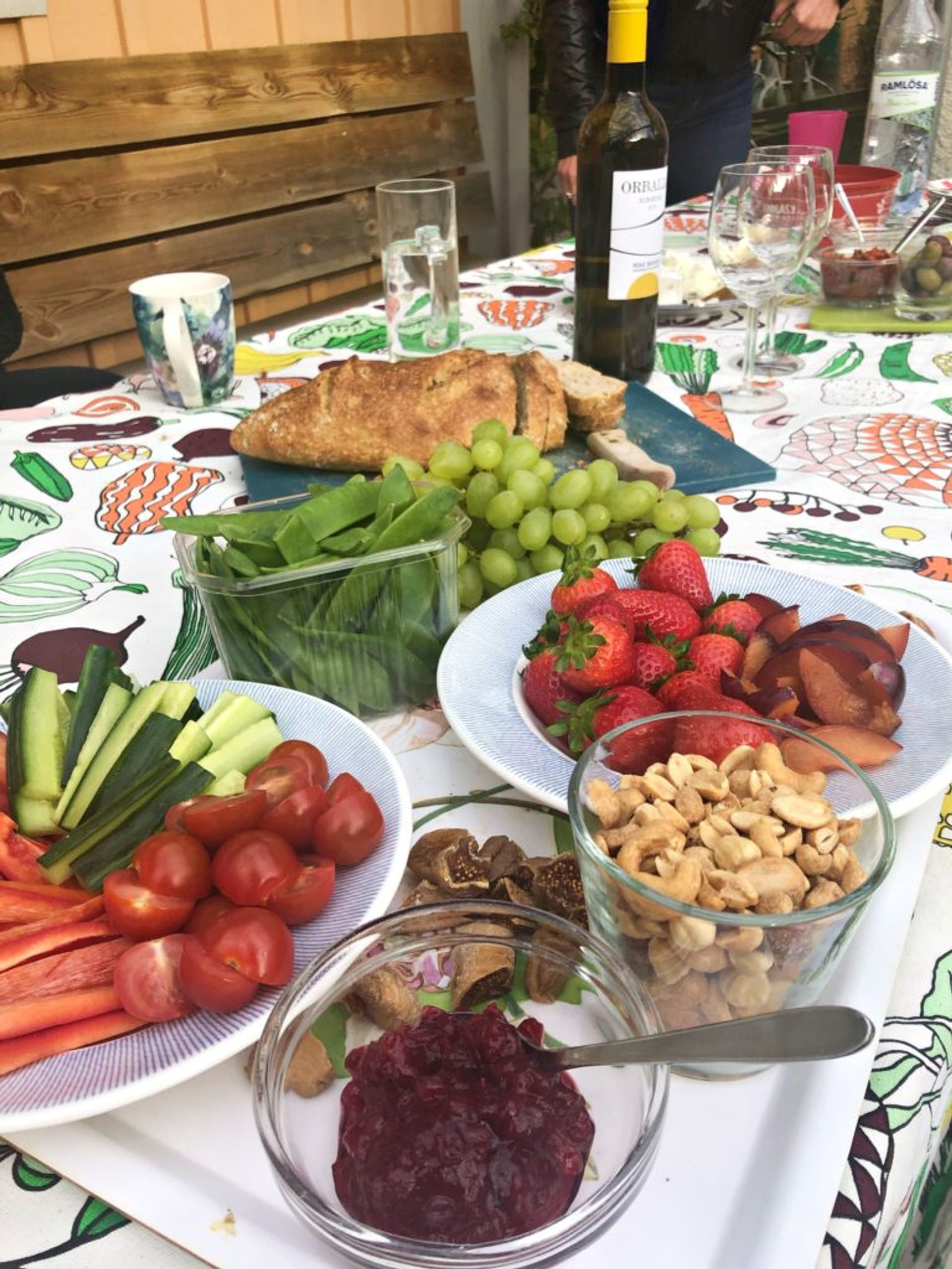 A table outside covered in plates of fresh fruit and vegetables.