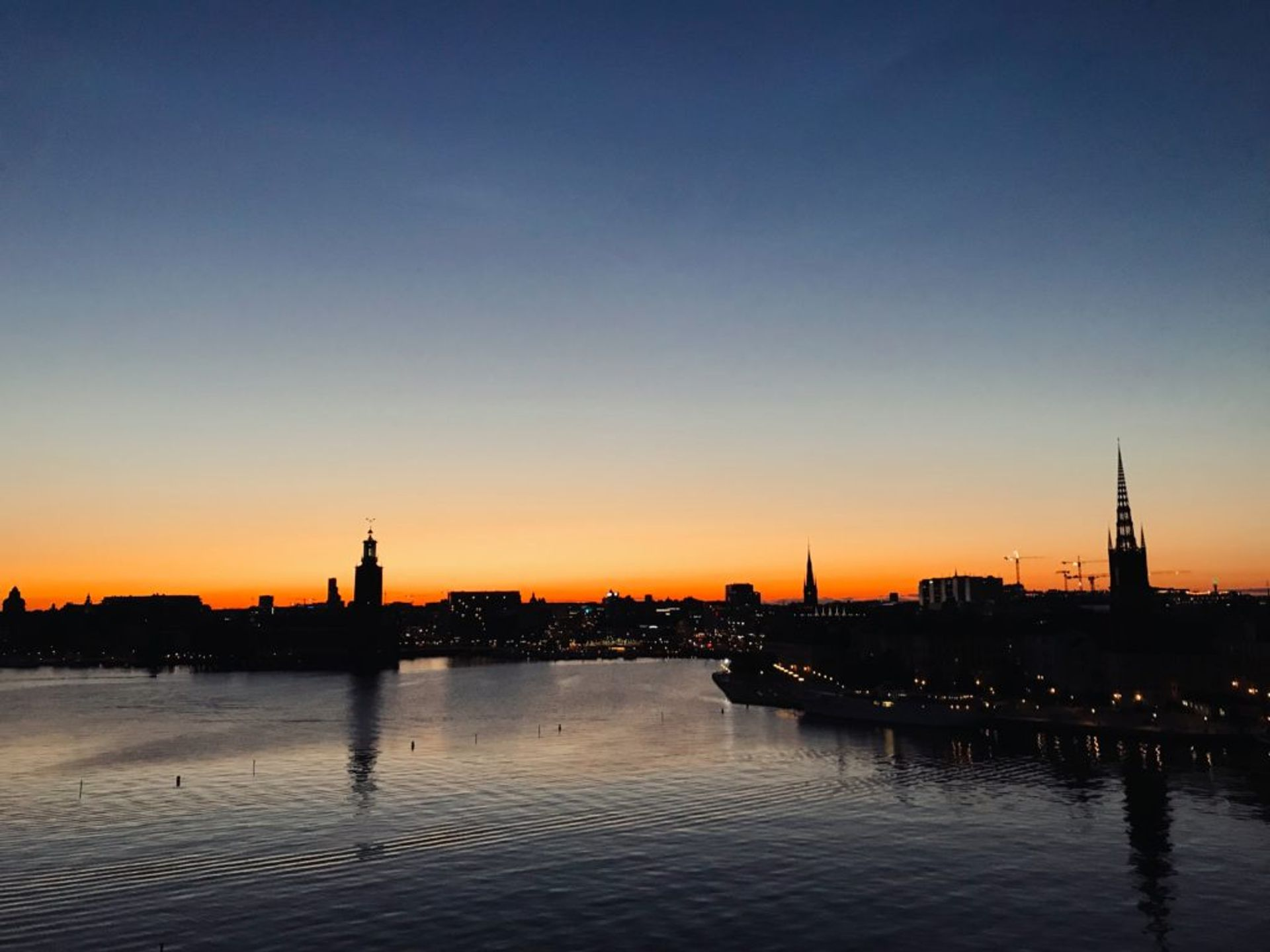 The Stockholm skyline silhouetted against a bright orange sunset.