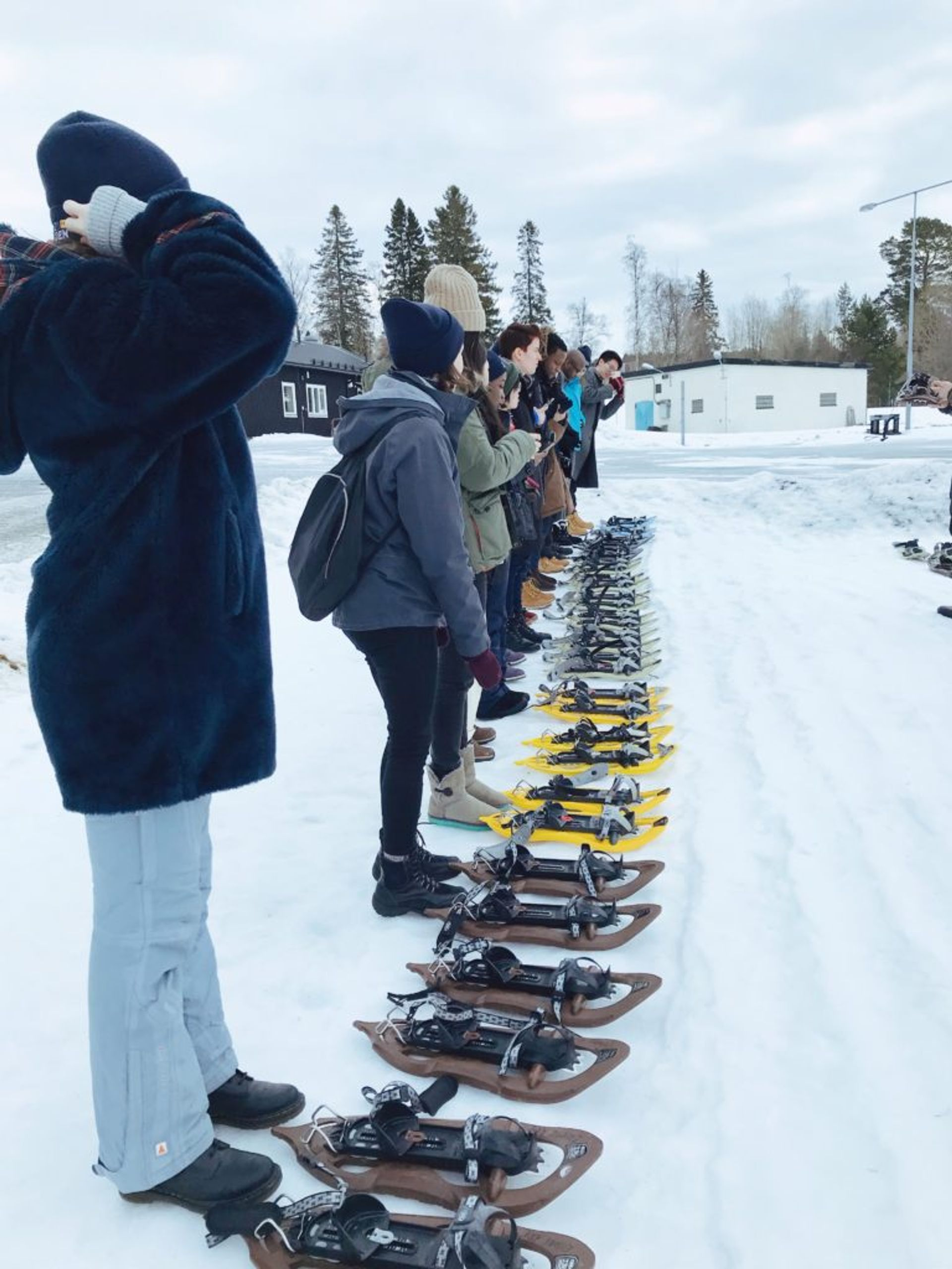 Students standing in a line with snowshoes set out in front of them. Some are taking photos of the snowshoes.