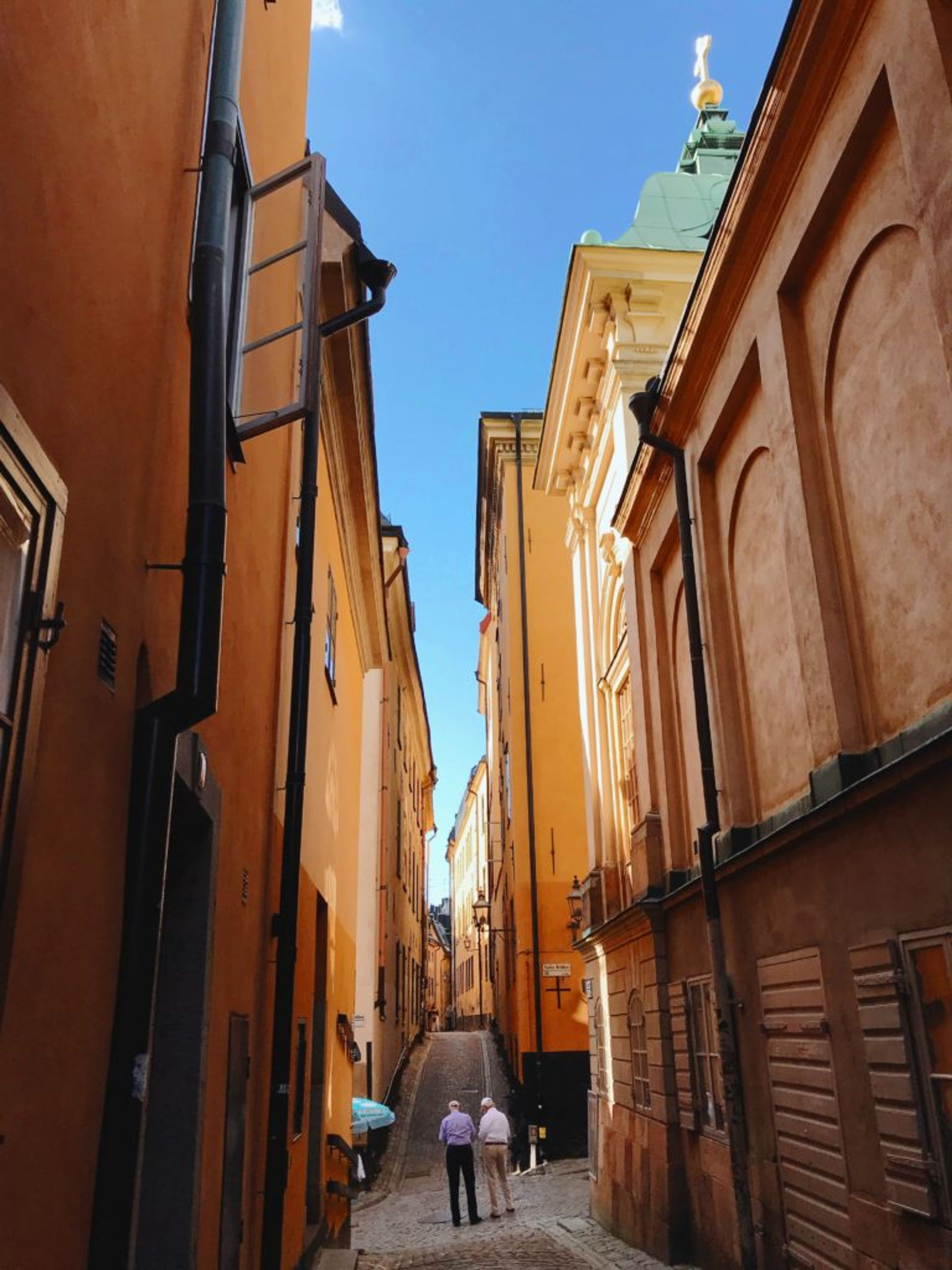 Two older men walking down a narrow, cobbled street in Stockholm's Old Town.