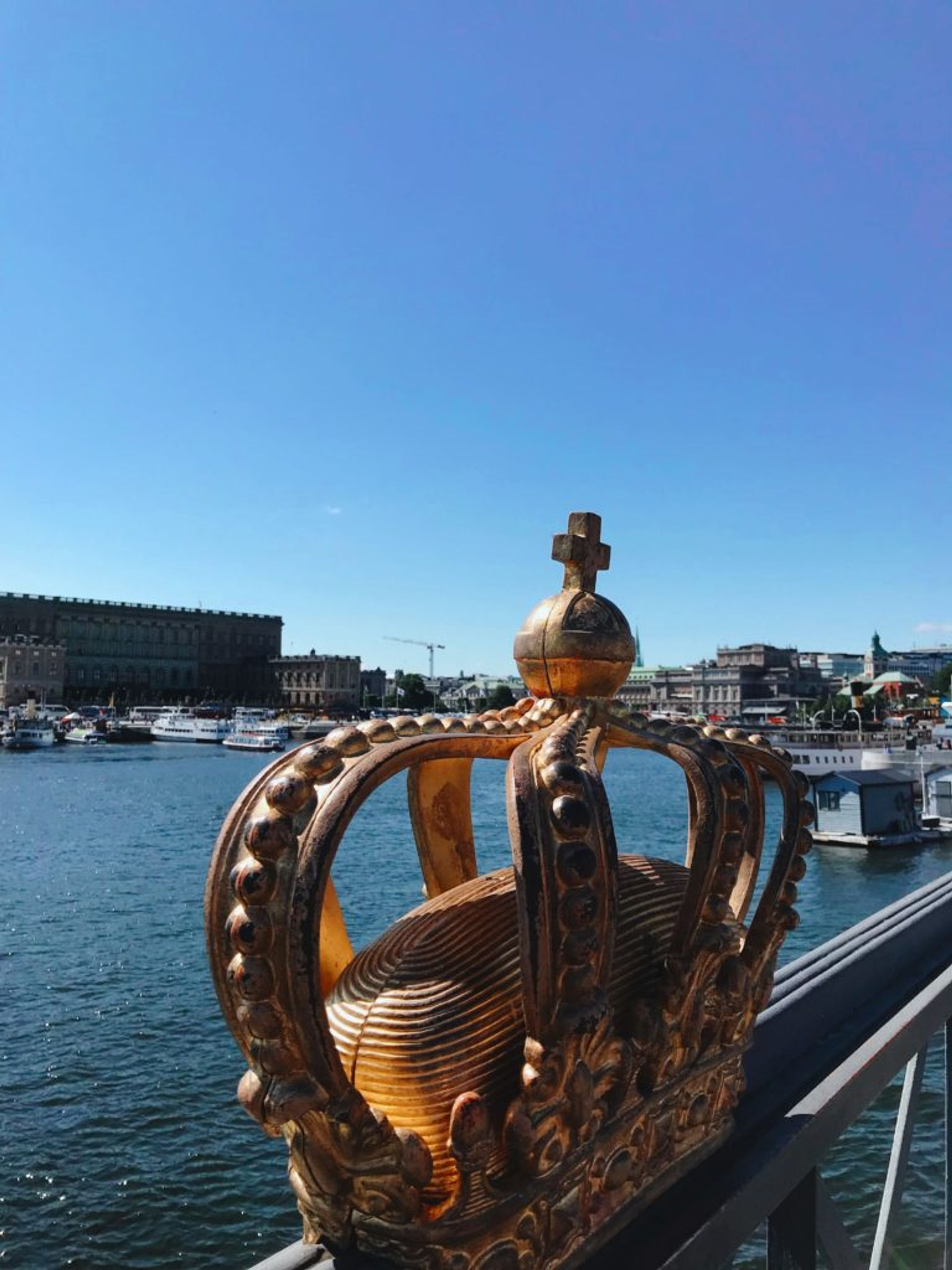 A gold coloured crown on a bridge in Stockholm.