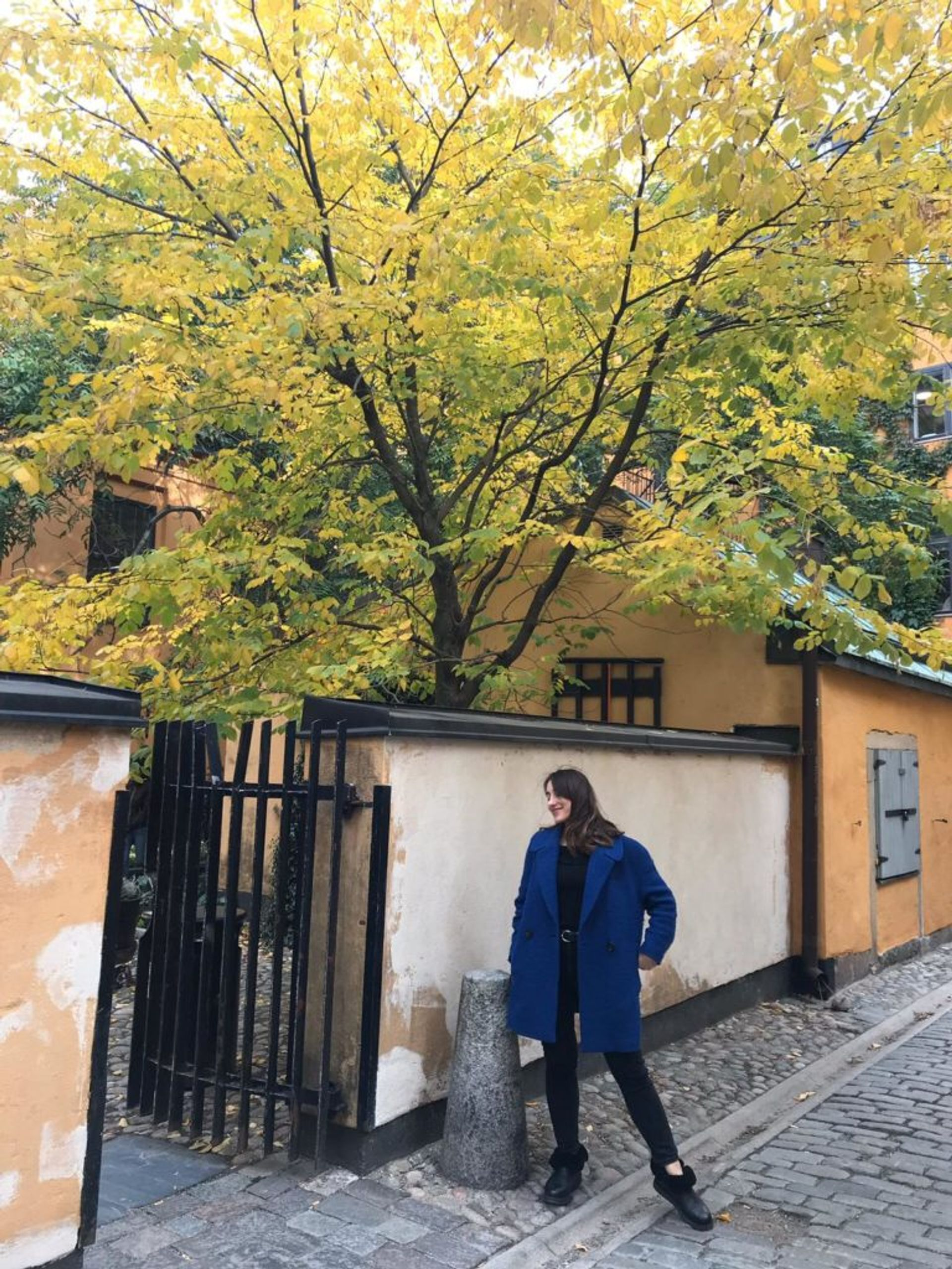 Hazal stands on a cobbled street in Stockholm's Old Town.