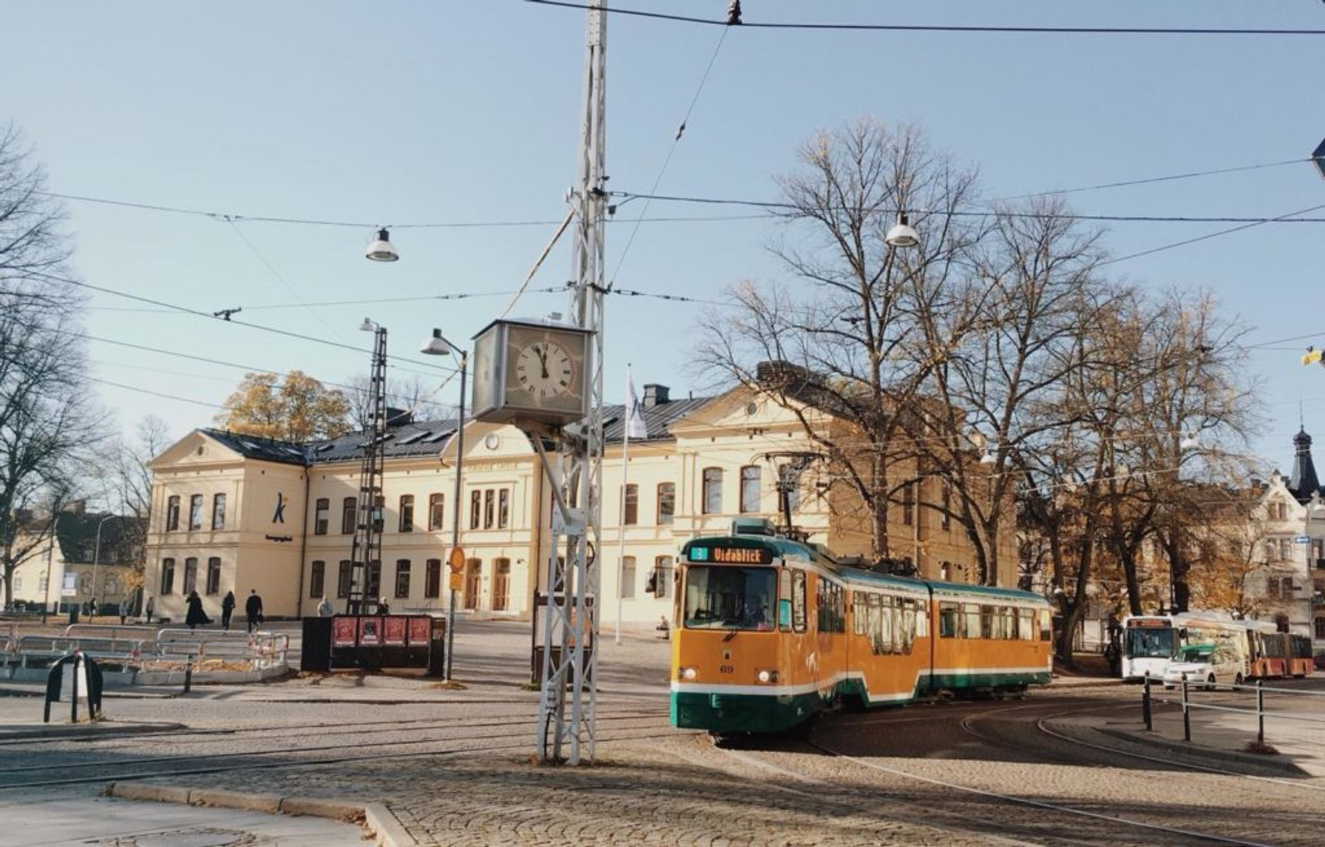 Yellow and green tram passing by a cream coloured building.