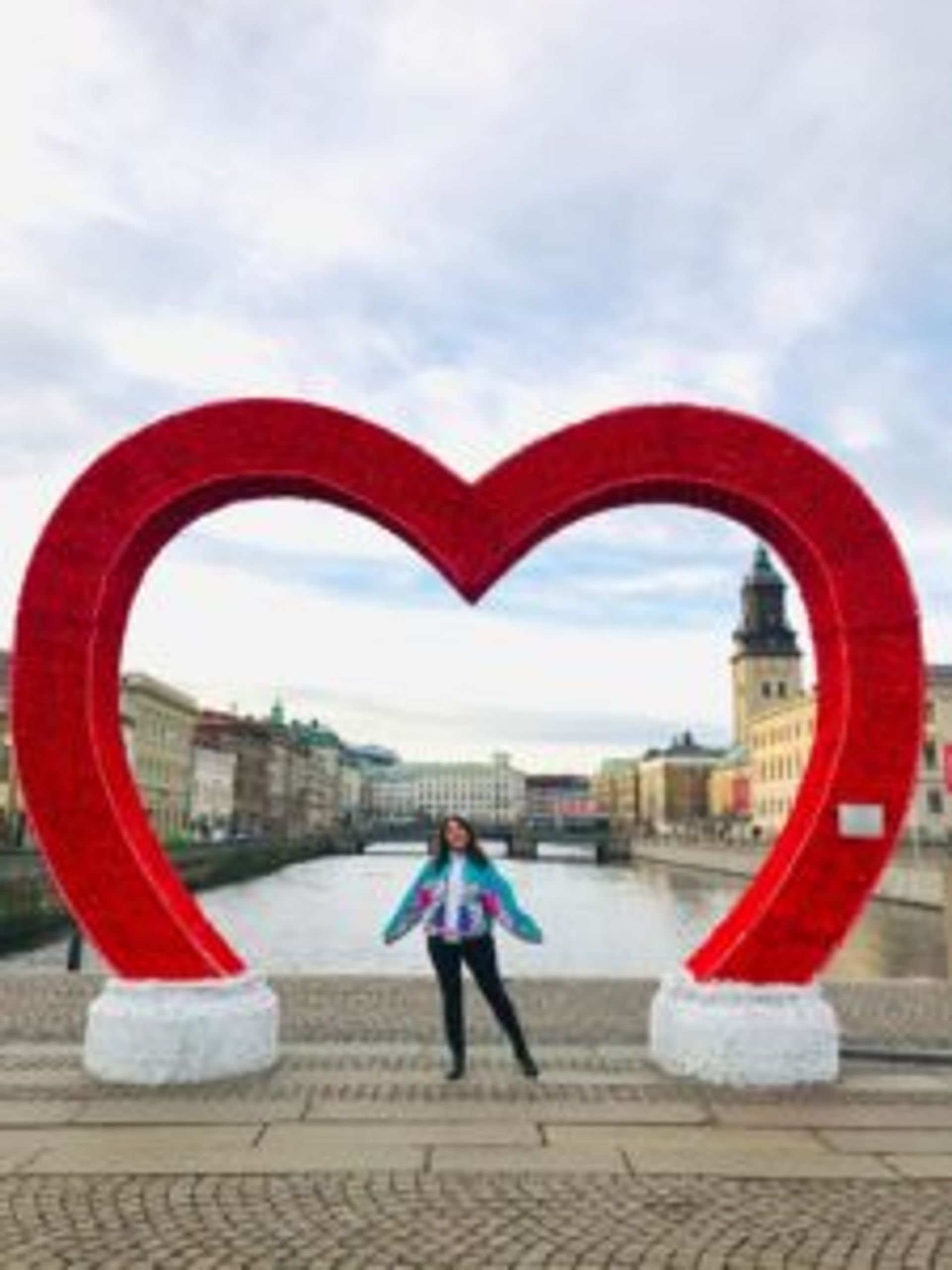 Hazal standing under a large, red heart Christmas decoration.