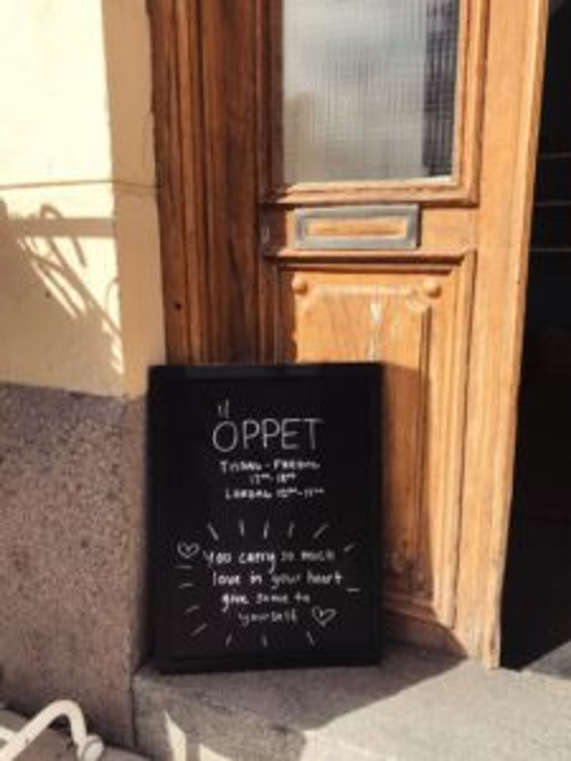 A wooden door with a sign outside. The sign says 'Öppet' which means Open in Swedish.