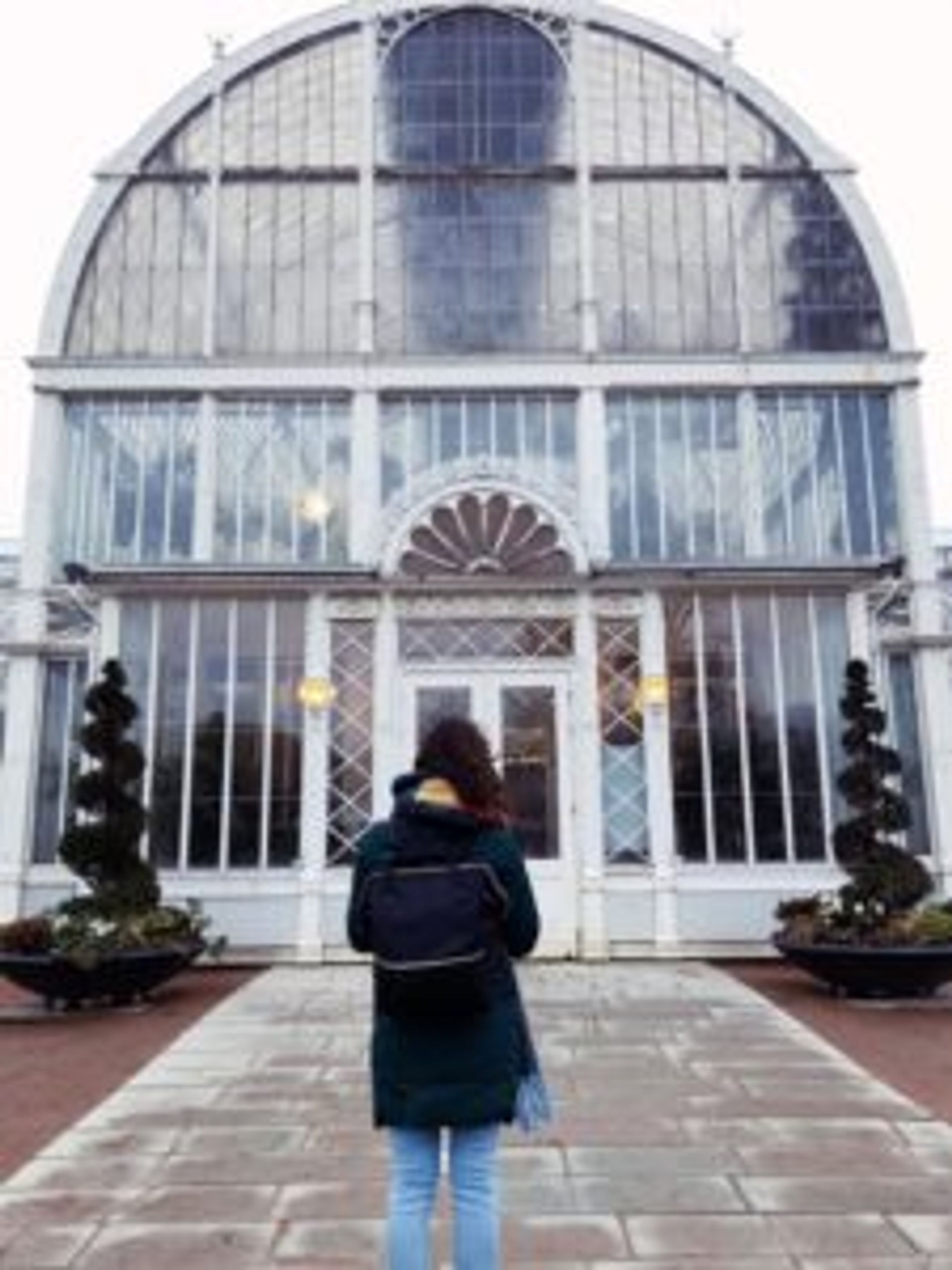 A person standing in front of the large, white greenhouse.
