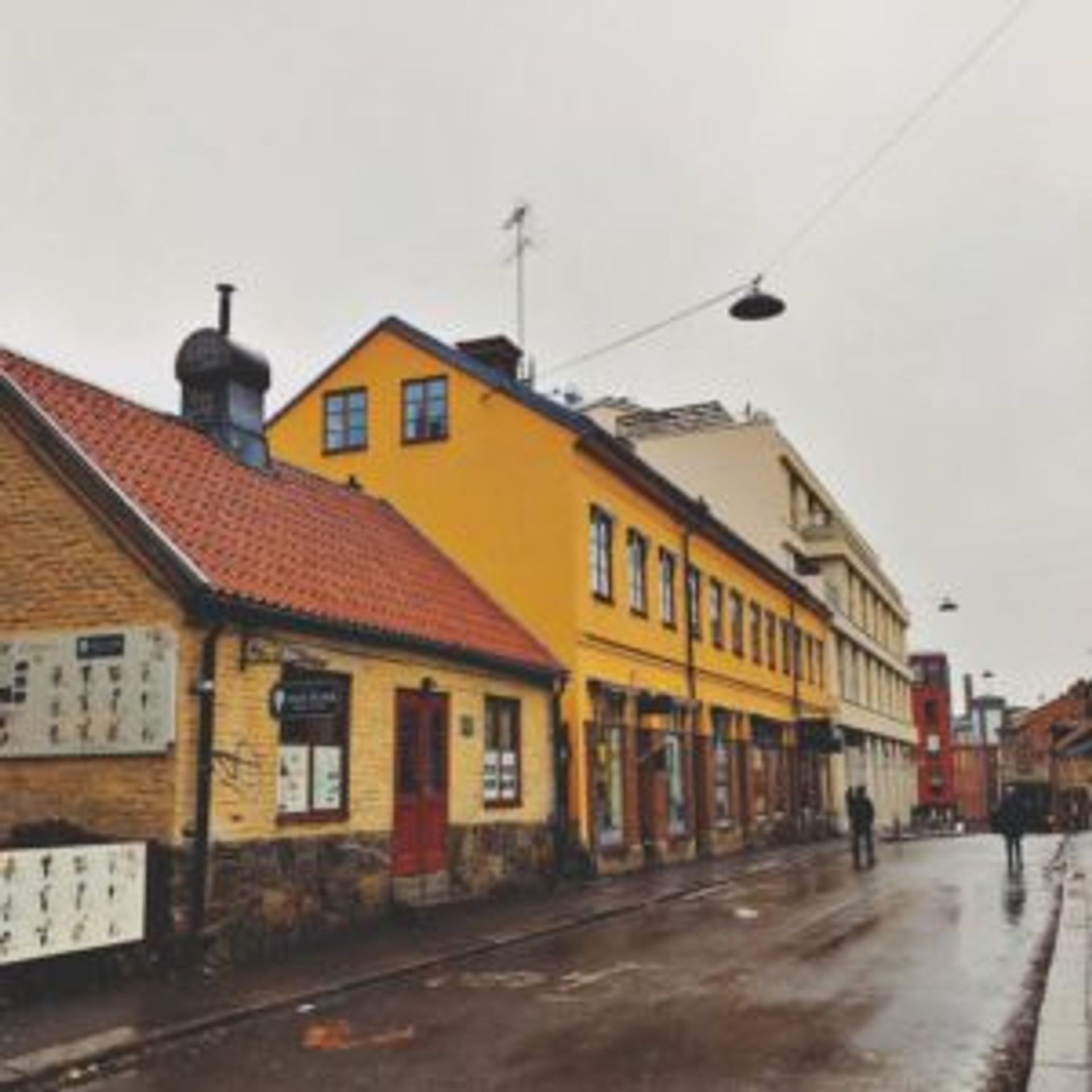 Old, colourful buildings along a road in Norrköping.