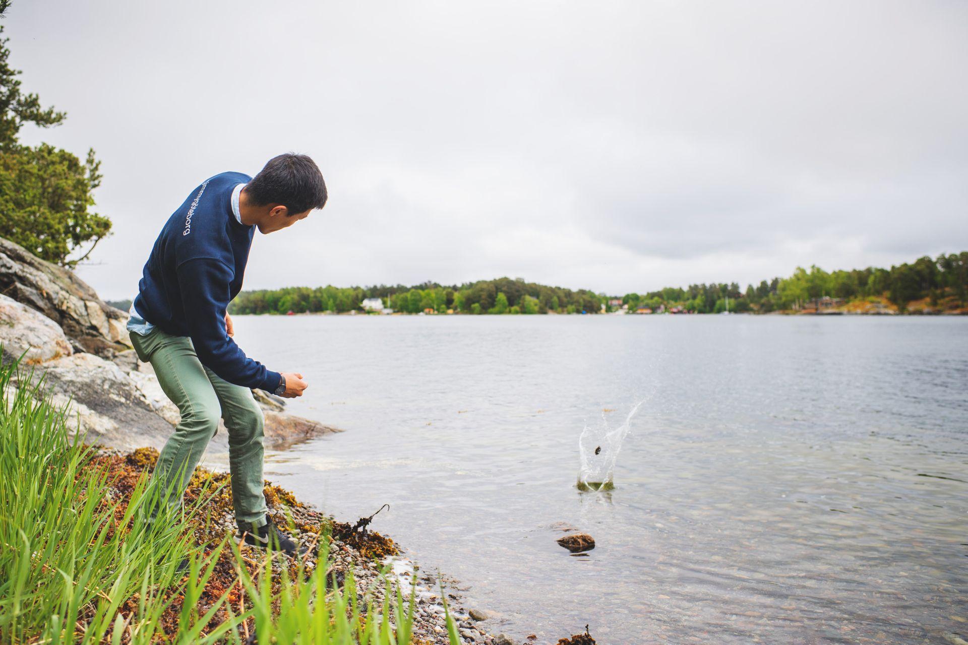 Man skimming stones on a lake.