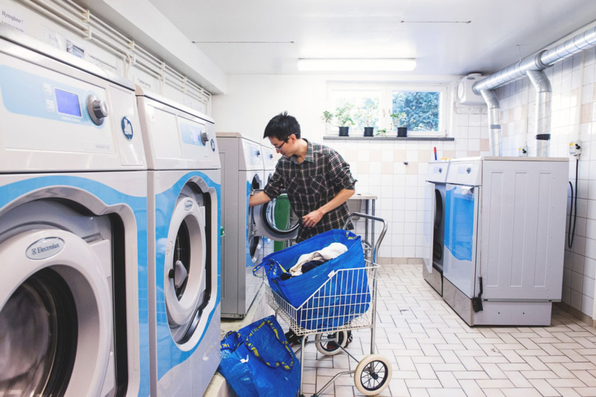 A student filling a large washing machine with dirty clothes in a laundry room.