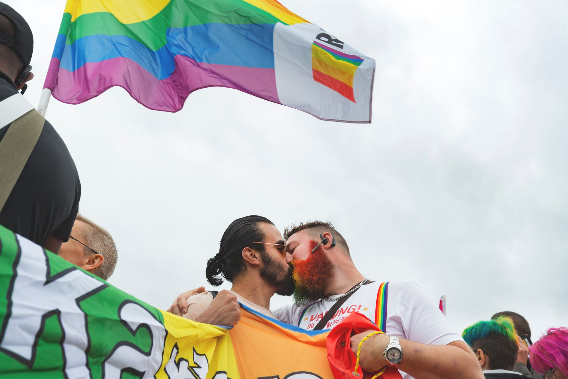 Two men kissing. They are holding a Pride flag and another Pride flag is waving beside them.