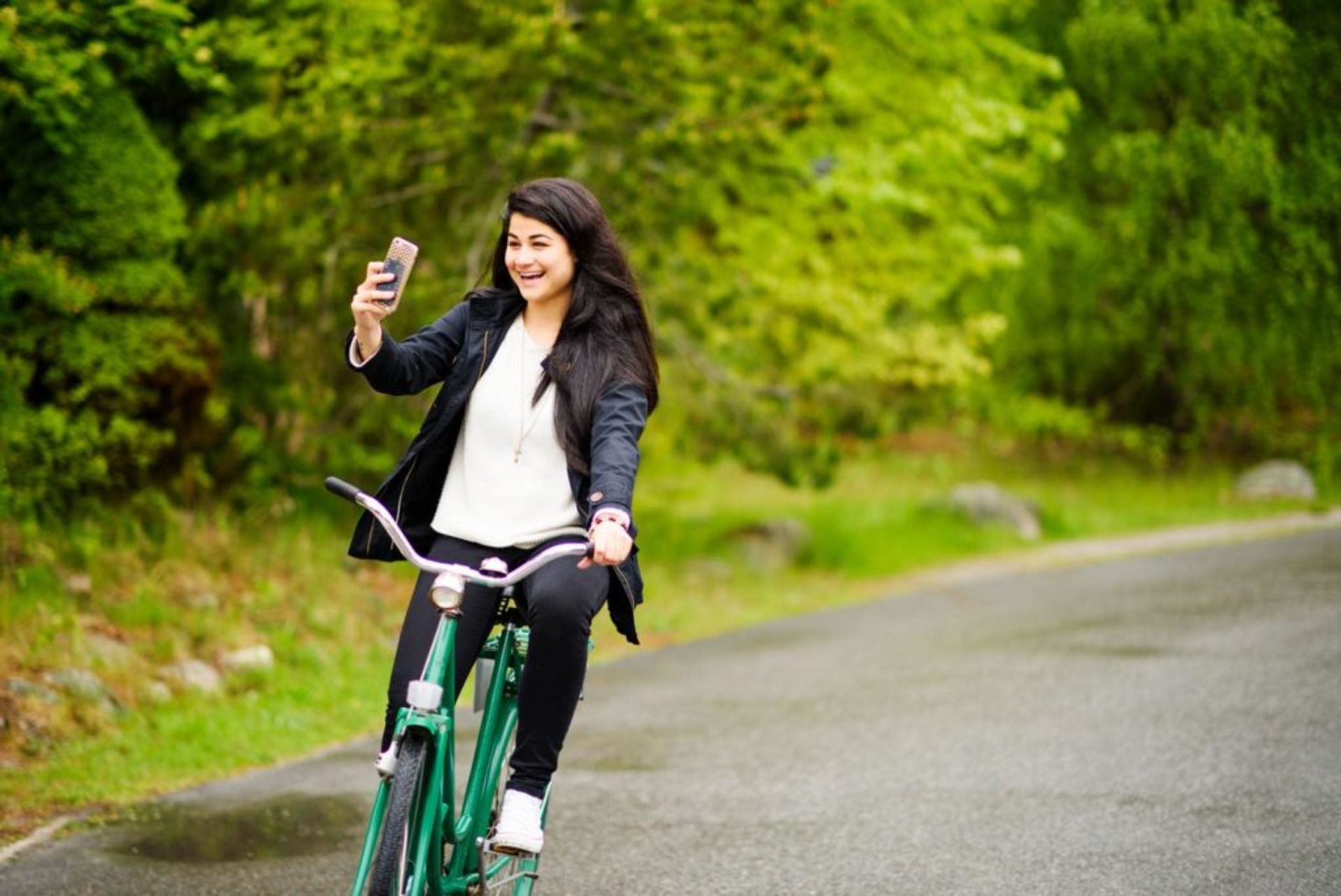 Marin cycles down a road on a green bicycle. She is holding a mobile phone in her right-hand.