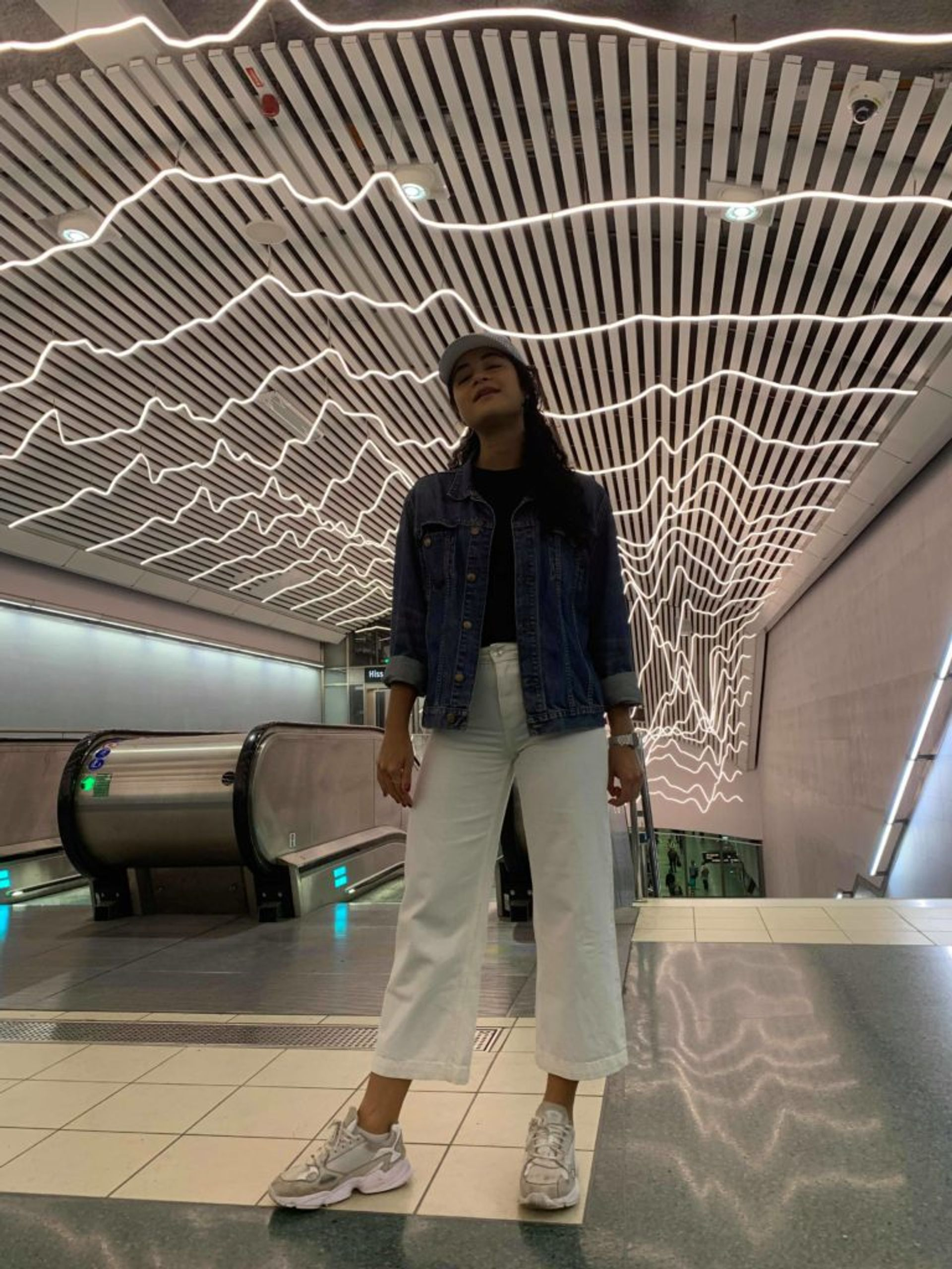 Marina stands in the Stockholm metro in cropped, white jeans, white sneakers and a denim jacket.