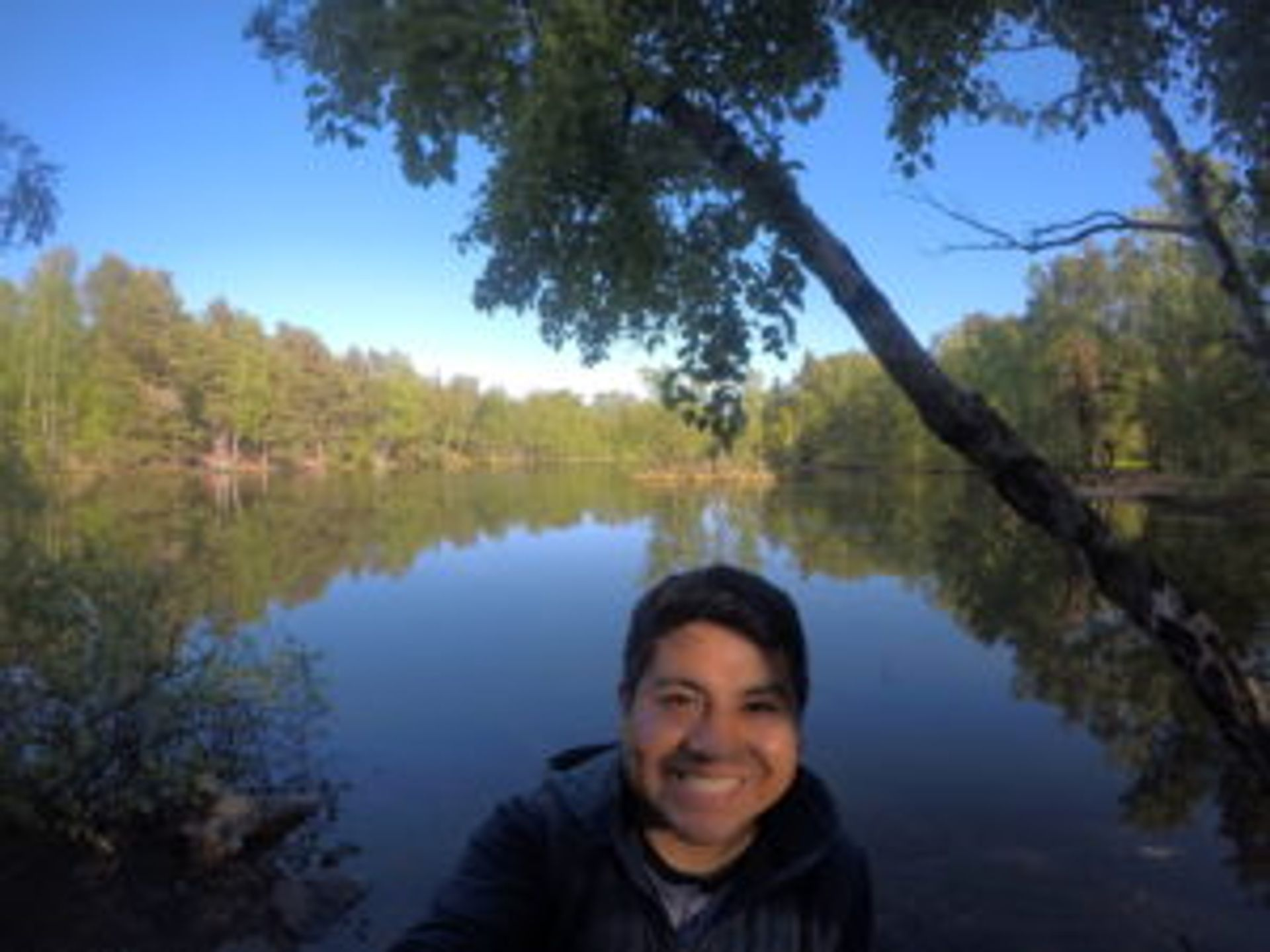 Camilo takes a selfie in front of the lake.