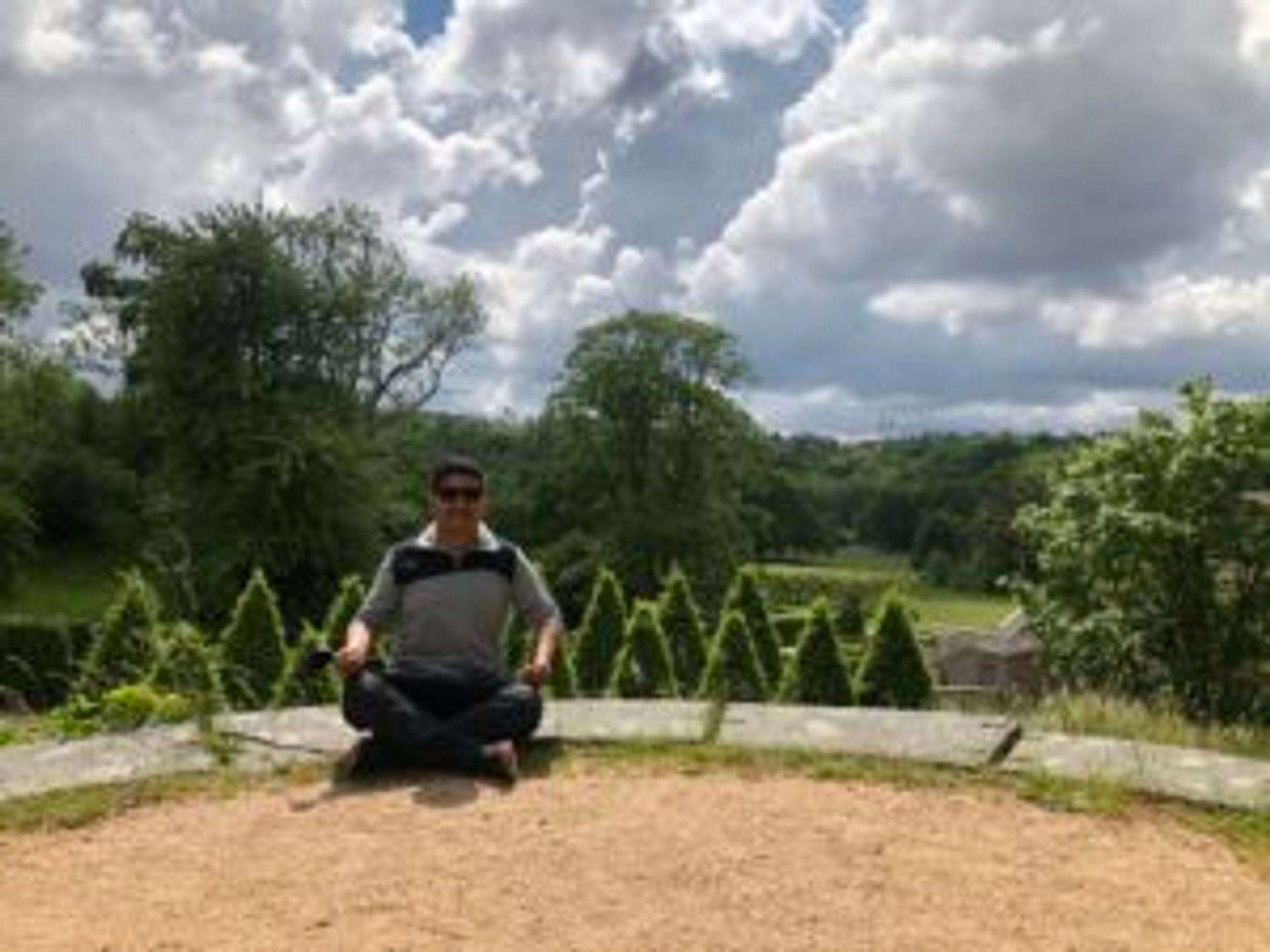 Camilo sits in the gardens at Gunnebo House.