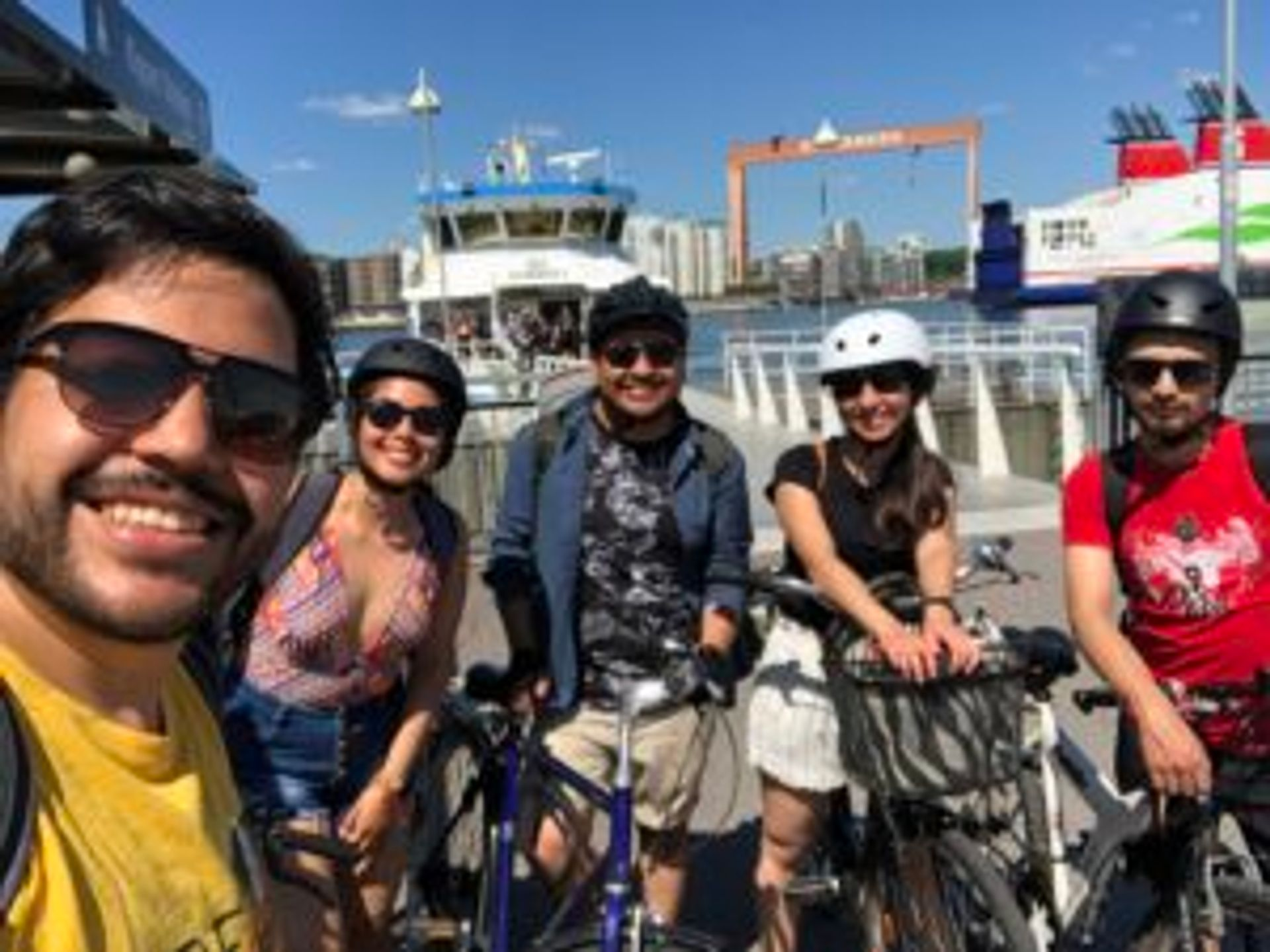 Camilo and three friends stand in front of a ferry with their bicycles.
