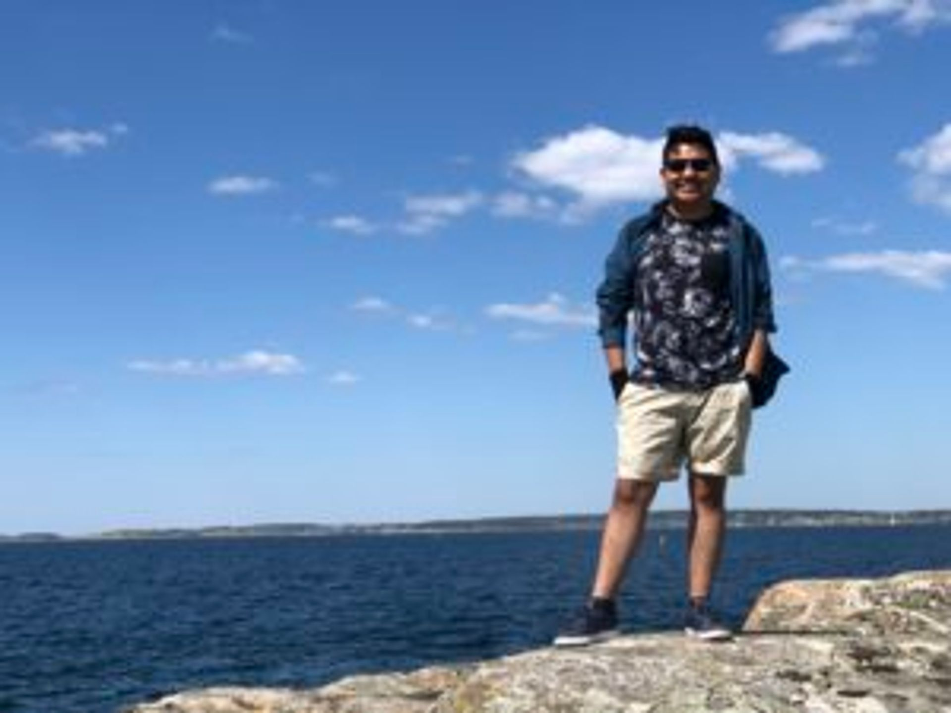 Camilo stands on a rock in front of the water.
