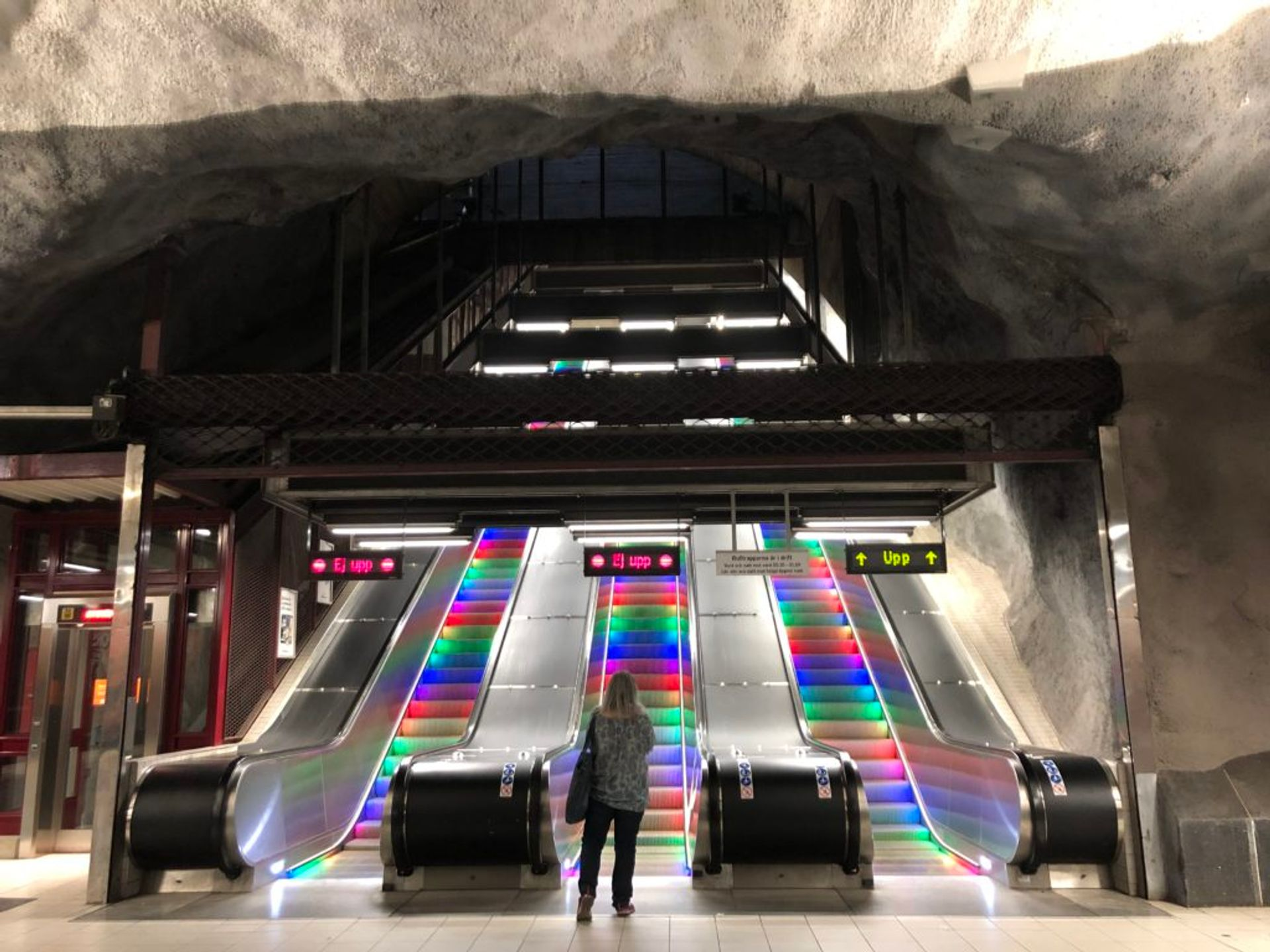 Three escalators in the Stockholm metro. The escalator steps are lit up in the colours of the rainbow.