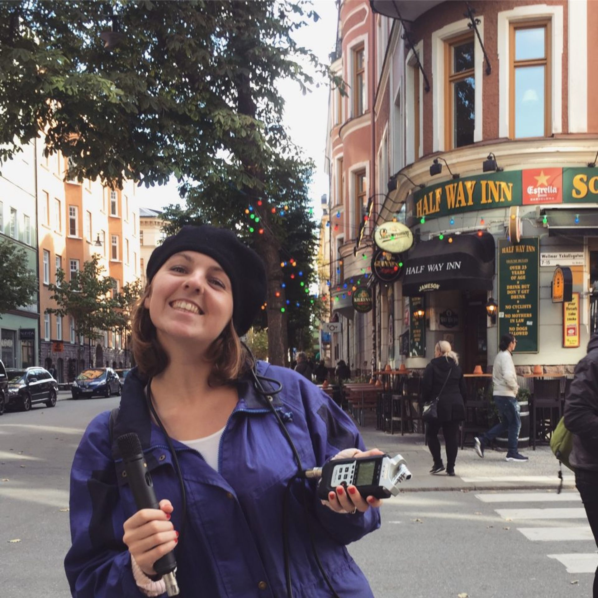 Emma holds a microphone in a street in Stockholm.