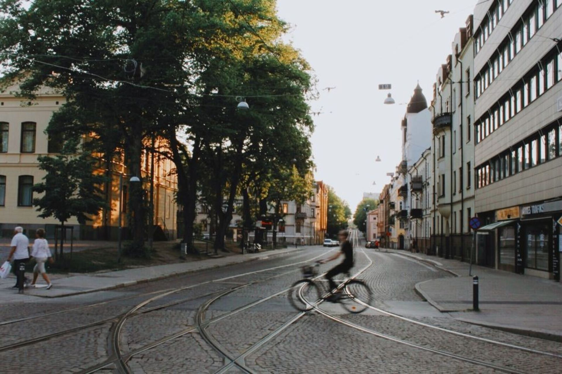 Person cycling across a cobbled street in Norrköping.