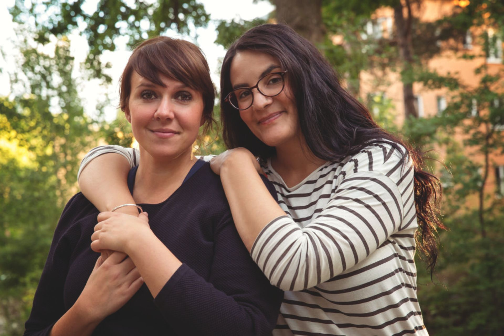 A couple stands outisde together. One woman has her arms around her girlfriend's shoulders.