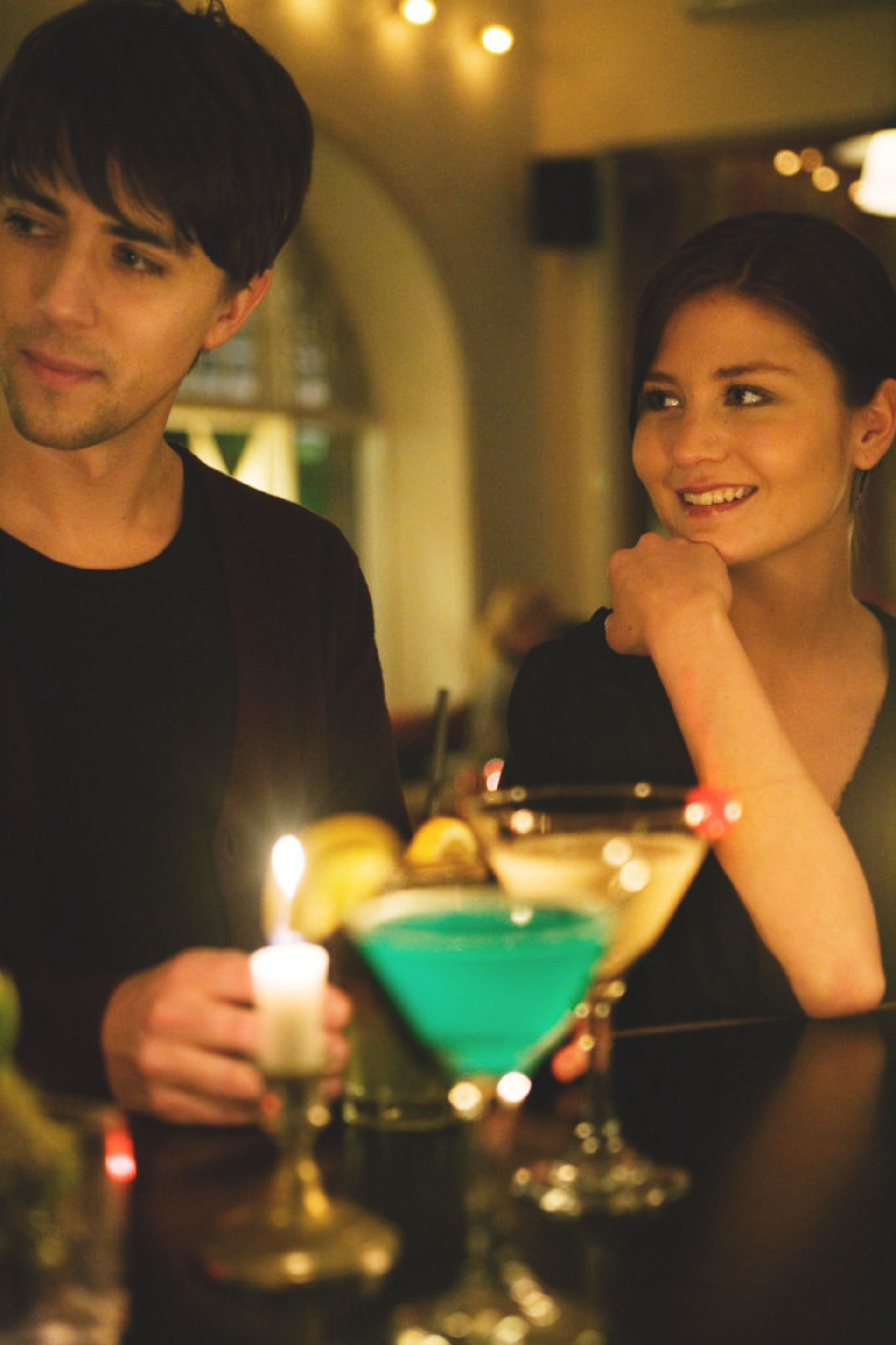 A man and woman having a date at a bar.