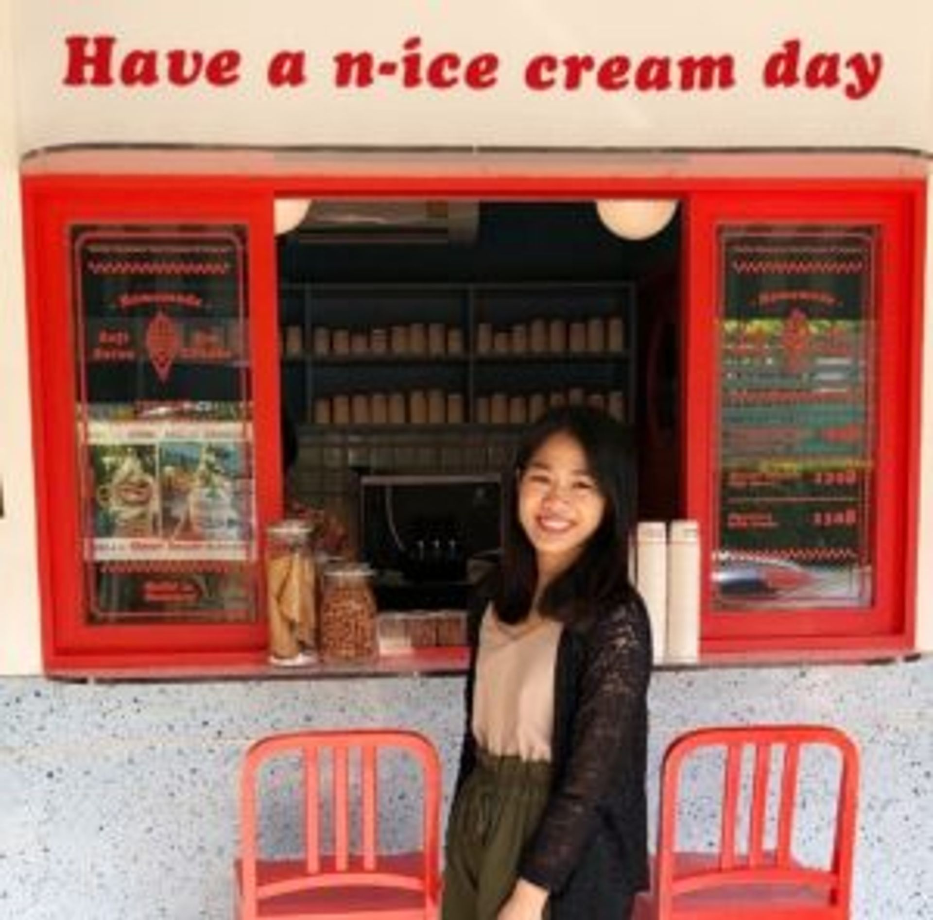 Arisa standing in front of a small ice-cream shop. The shop has a sign that reads 'Have a n-ice cream day'.