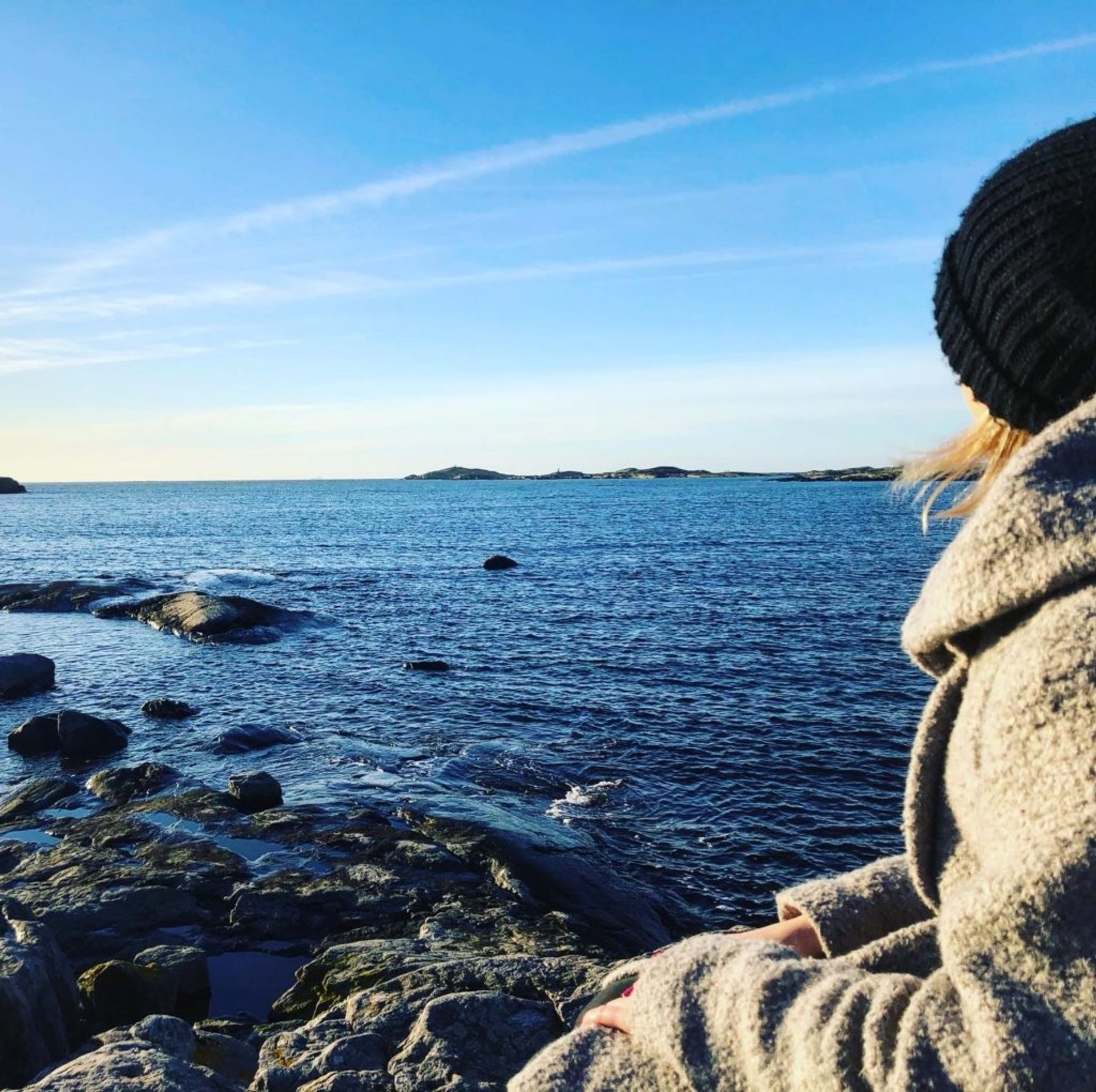 Sara, dressed in a winter coat and hat, sits on a rock by the sea staring out at the view.