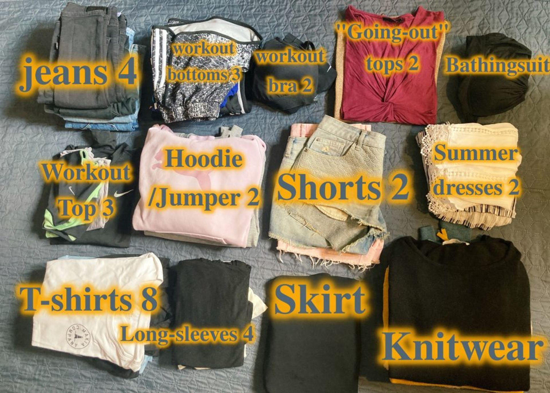 A mixture of different clothing including jeans, knitwear, dresses, shorts.