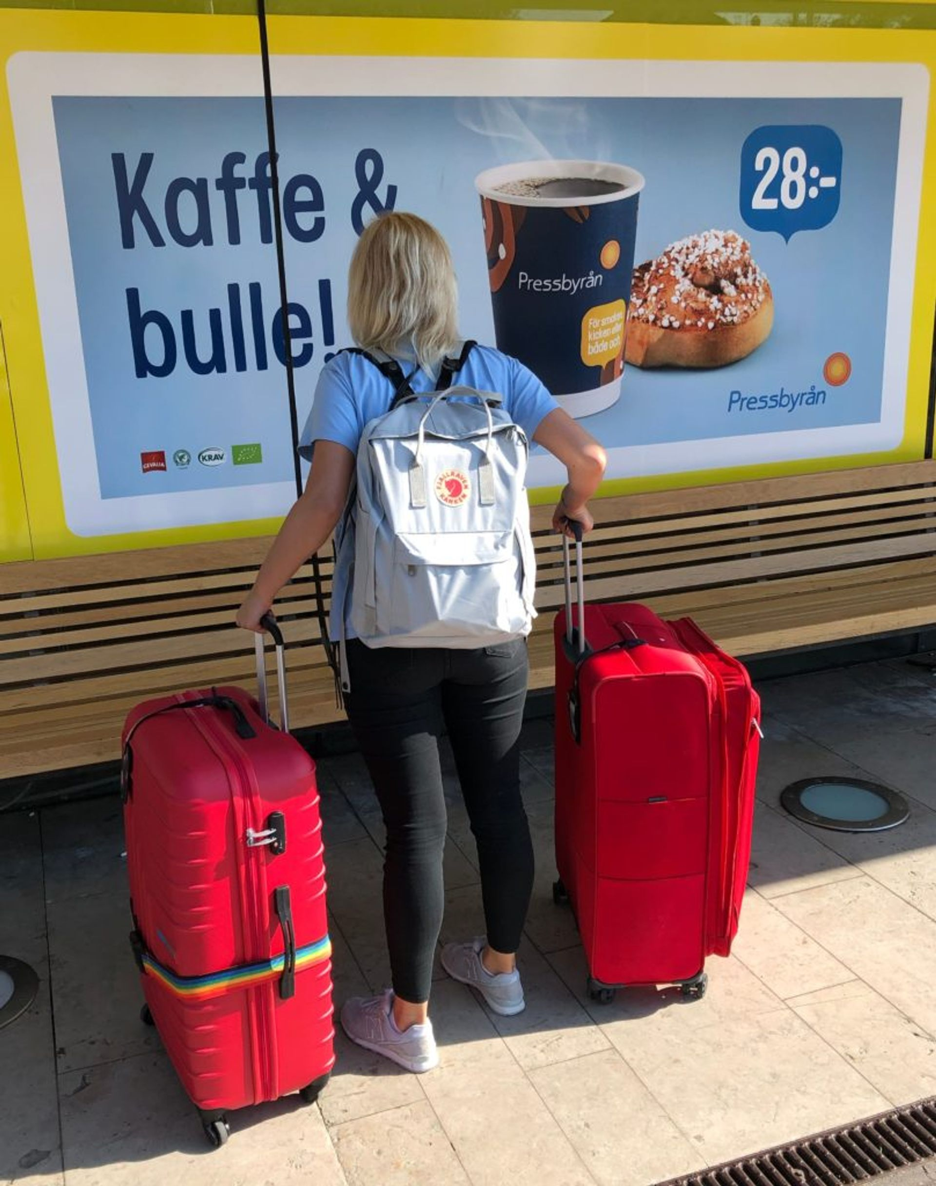 Sara stands in front of a shop at the airport in Sweden holding two large red suitcases.